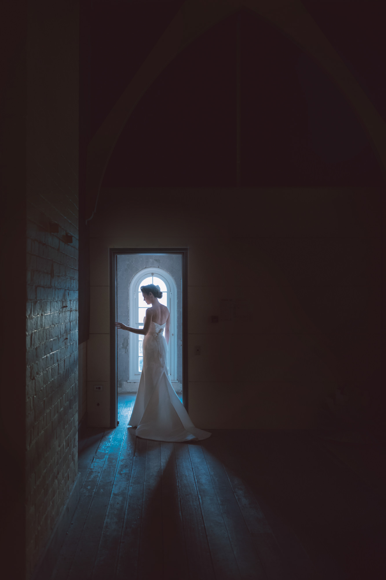Moody photo of bride framed in doorway, by Studio Impressions Photography