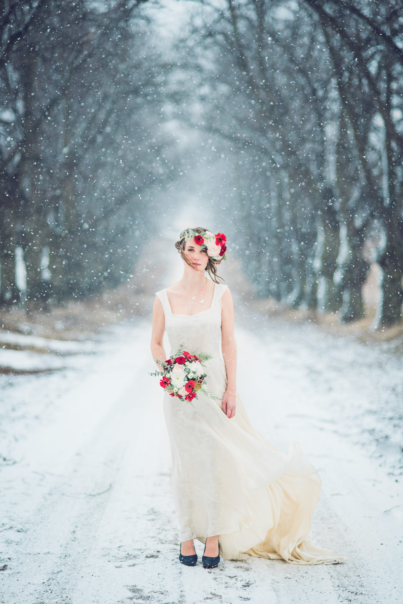 Winter wedding bride wearing sleeveless dress with rose bouquet photo by Nordica Photography