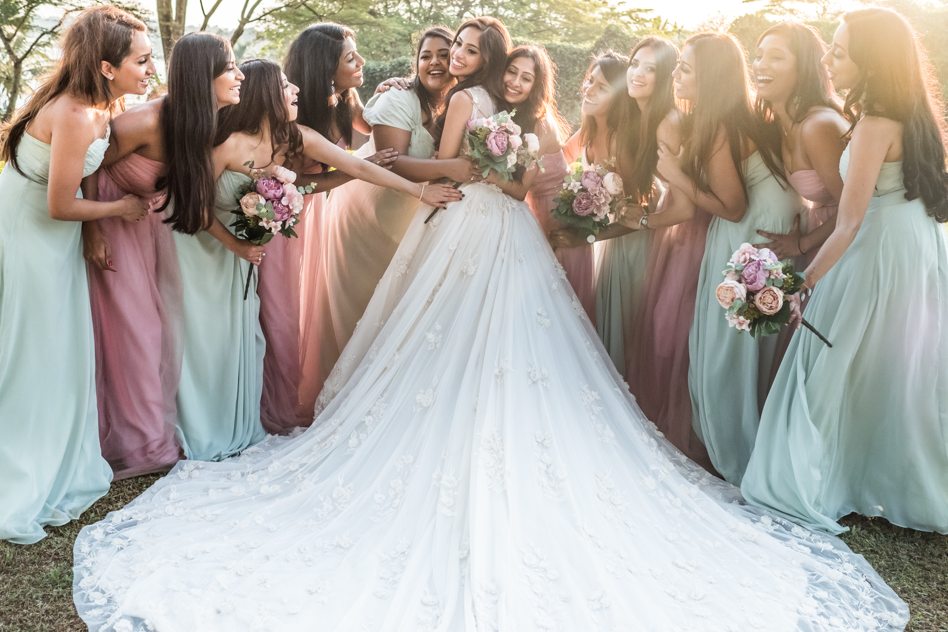 Bride wearing long train embraced by bridesmaids - photo by Sephi Bergerson