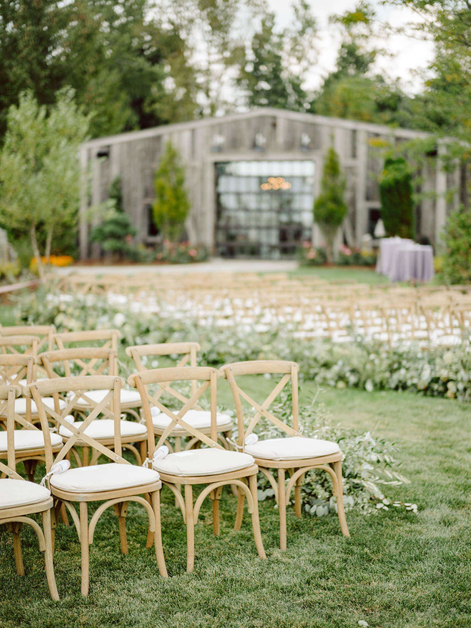 Outdoor reception decor with wood cross back chairs - photo by Benj Haisch