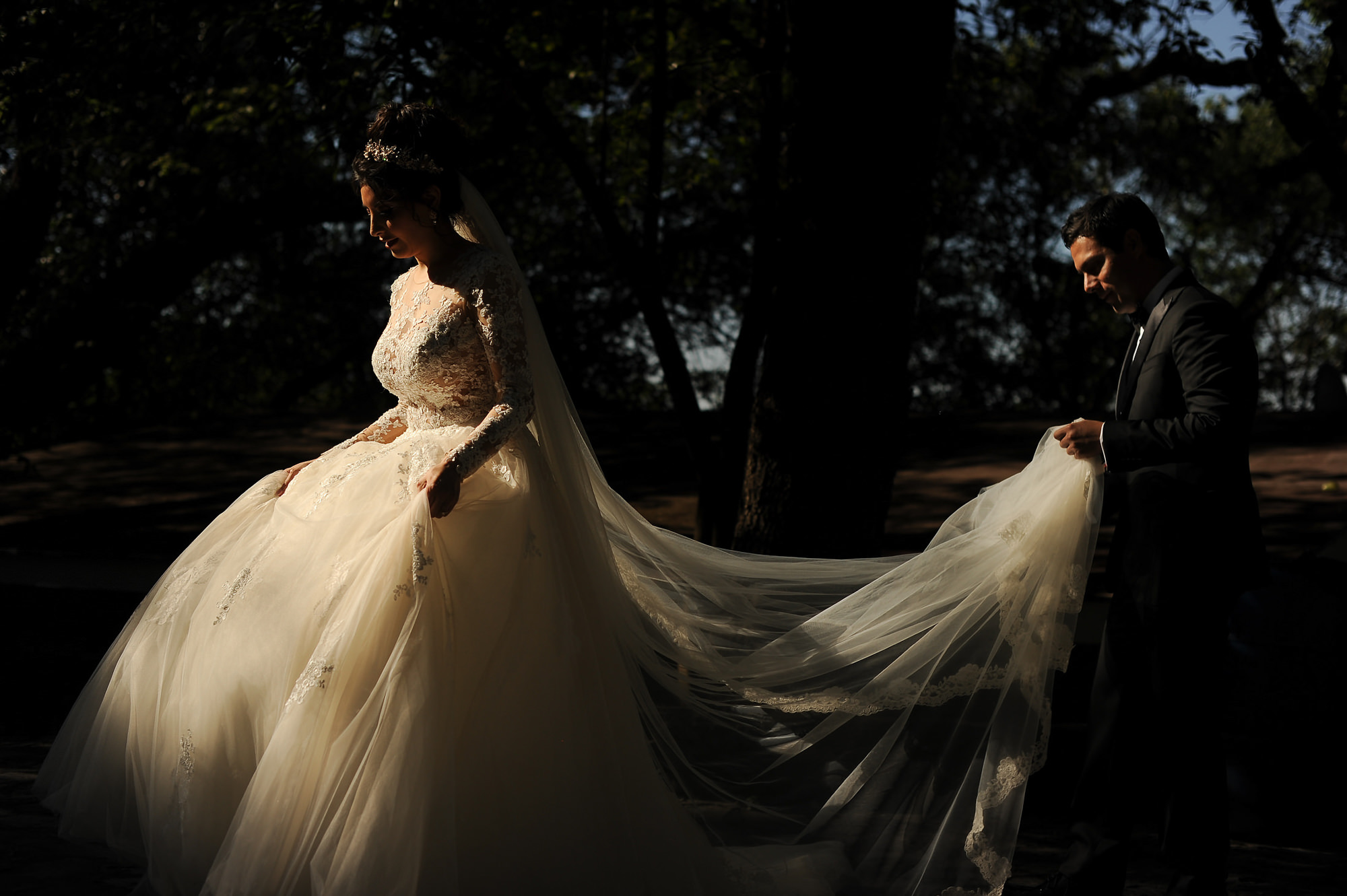 Groom carrying brides veil and train in beautiful light - photo by Daniel Aguilar