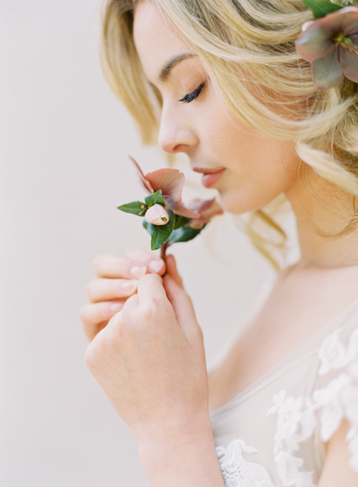 Profile of bride  wearing floral hairstyle smelling flower Jen Huang Los Angeles wedding photographer