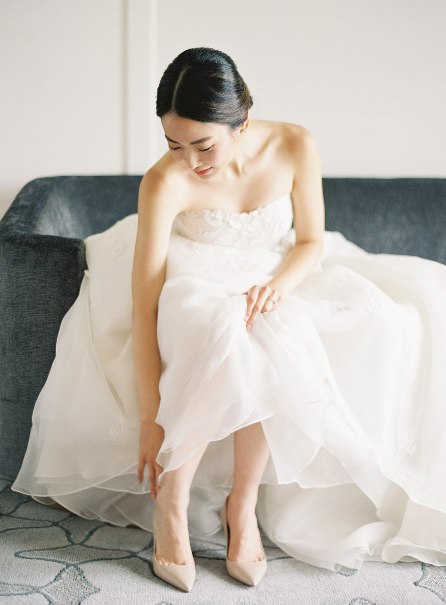 Bride in strapless lace wedding dress putting on nude shoes Jen Huang Los Angeles wedding photographer