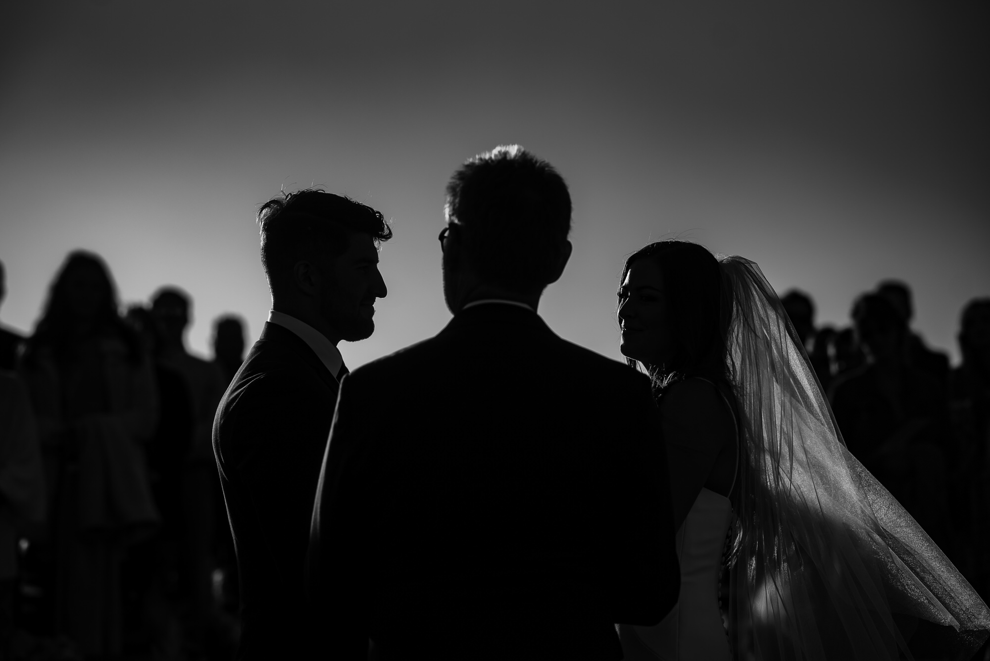 Silhouette of couple and officiant during ceremony  - photo by Tyler Wirken