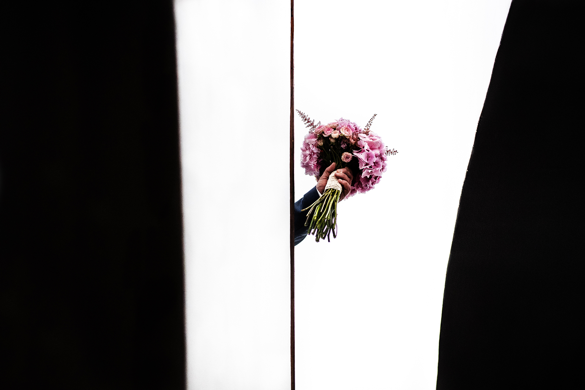 Detail of groom holding bouquet - photo by Victor Lax