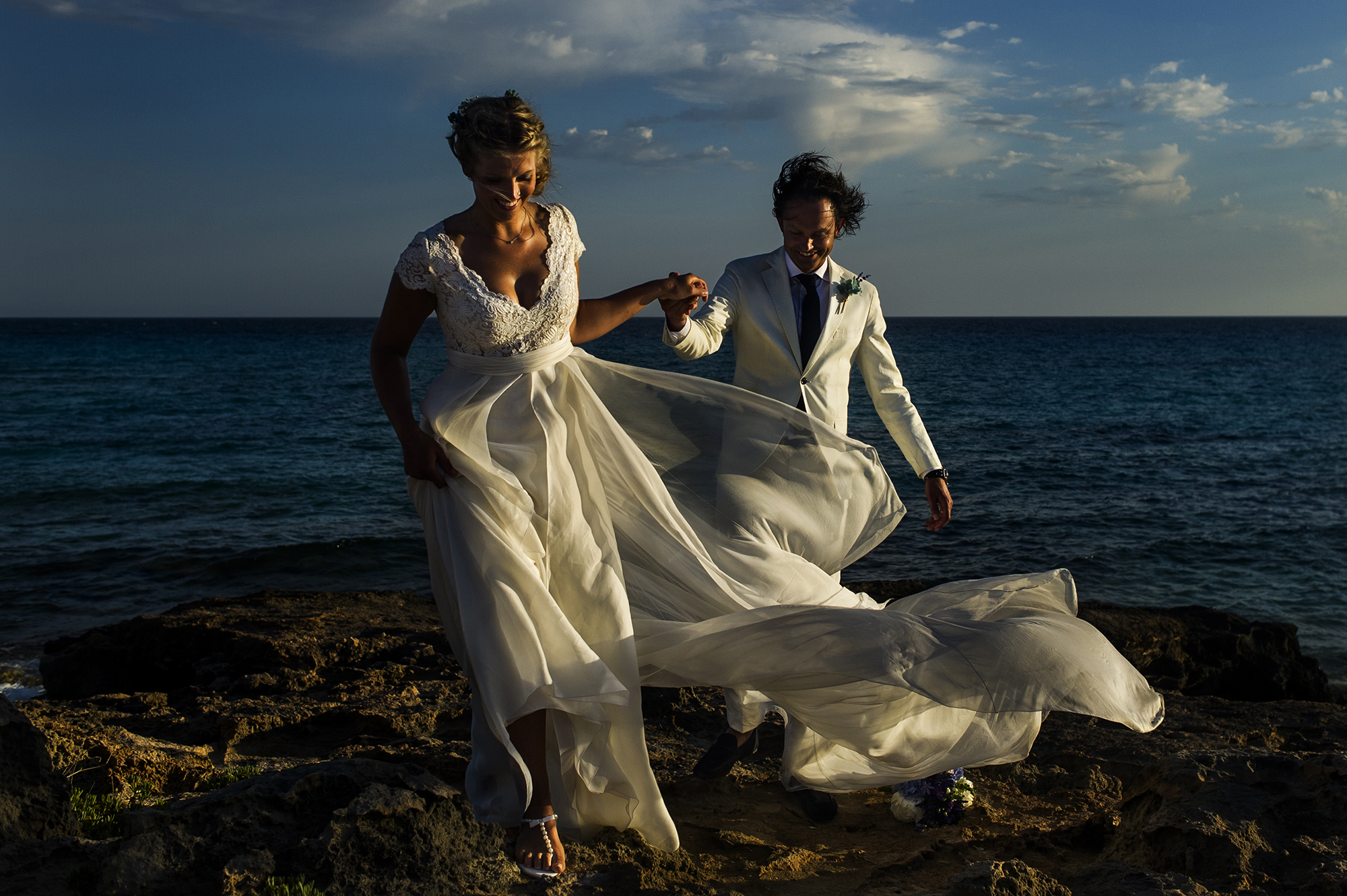 Beautiful bride and groom in white suit on beach - photo by Victor Lax