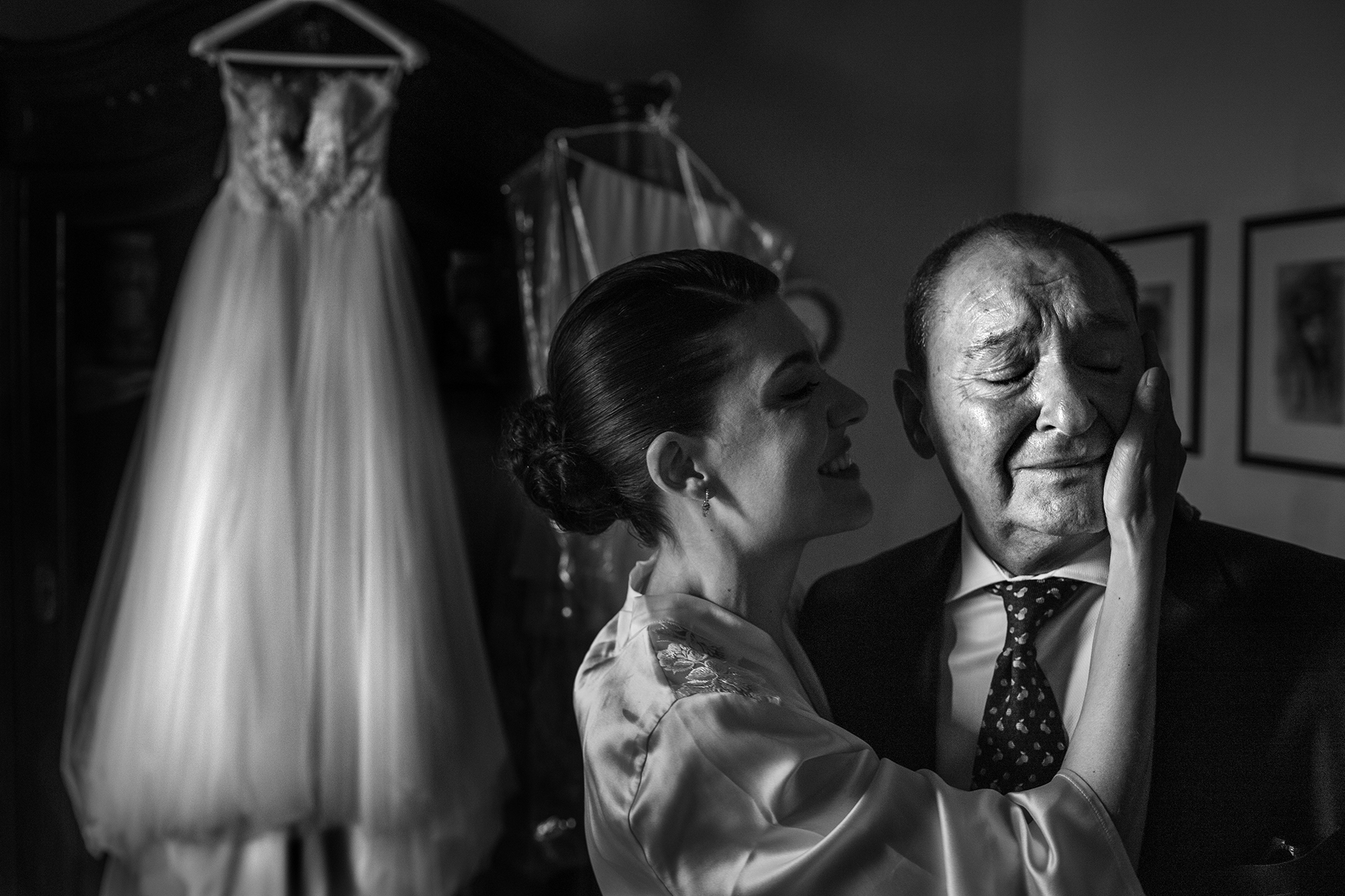 Bride touching dad's tearful face - photo by Victor Lax