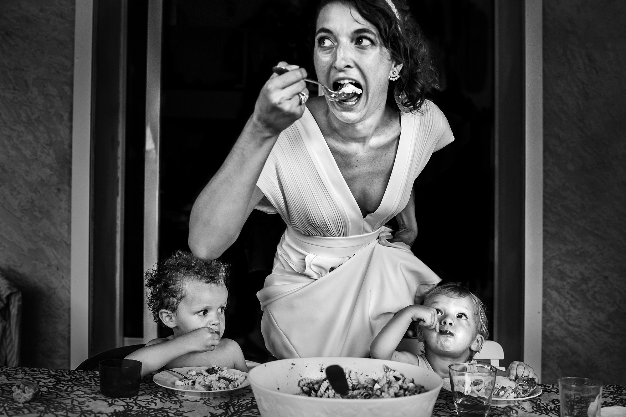 Candid of bride sneaking a bite with the kids - photo by Victor Lax