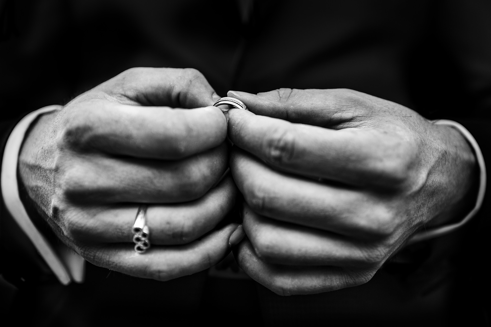 Closeup of hands holding rings - photo by Victor Lax