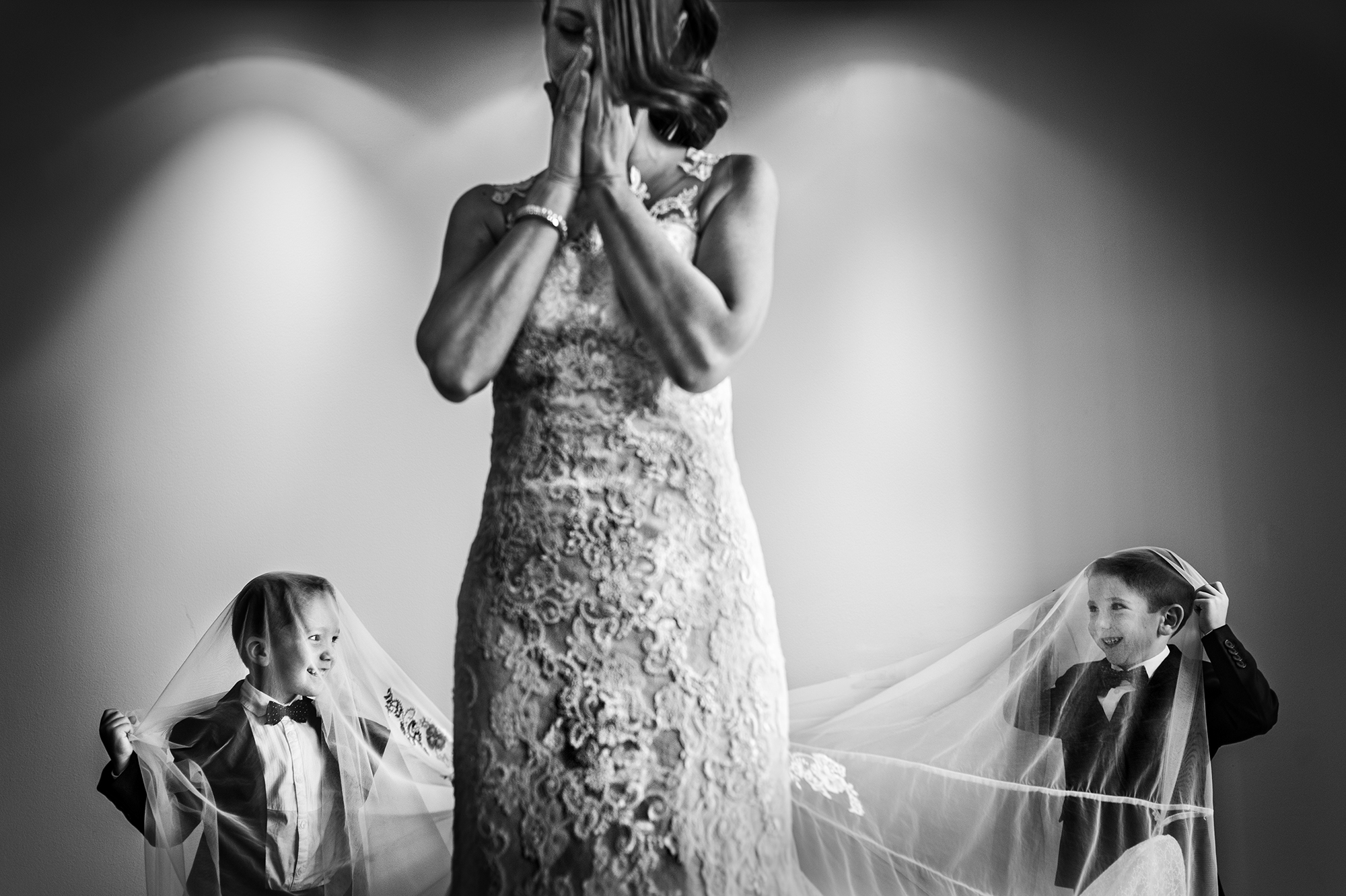 Cute ringbearers under bridal veil - photo by Victor Lax