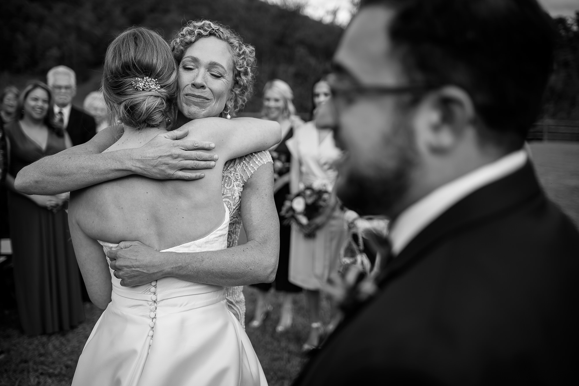 Mom and bride caress at wedding ceremony - Photo by Tyler Wirken - Kansas City