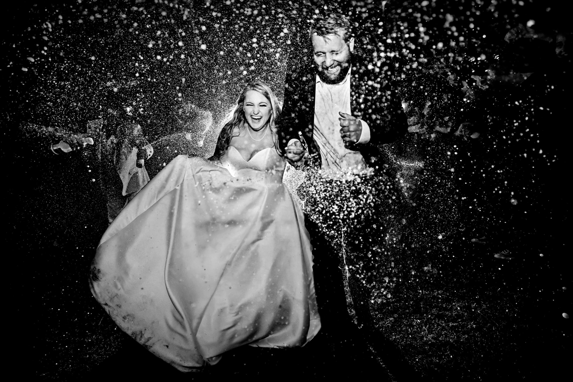 Bride and groom run through snow - photo by Two Mann Studios