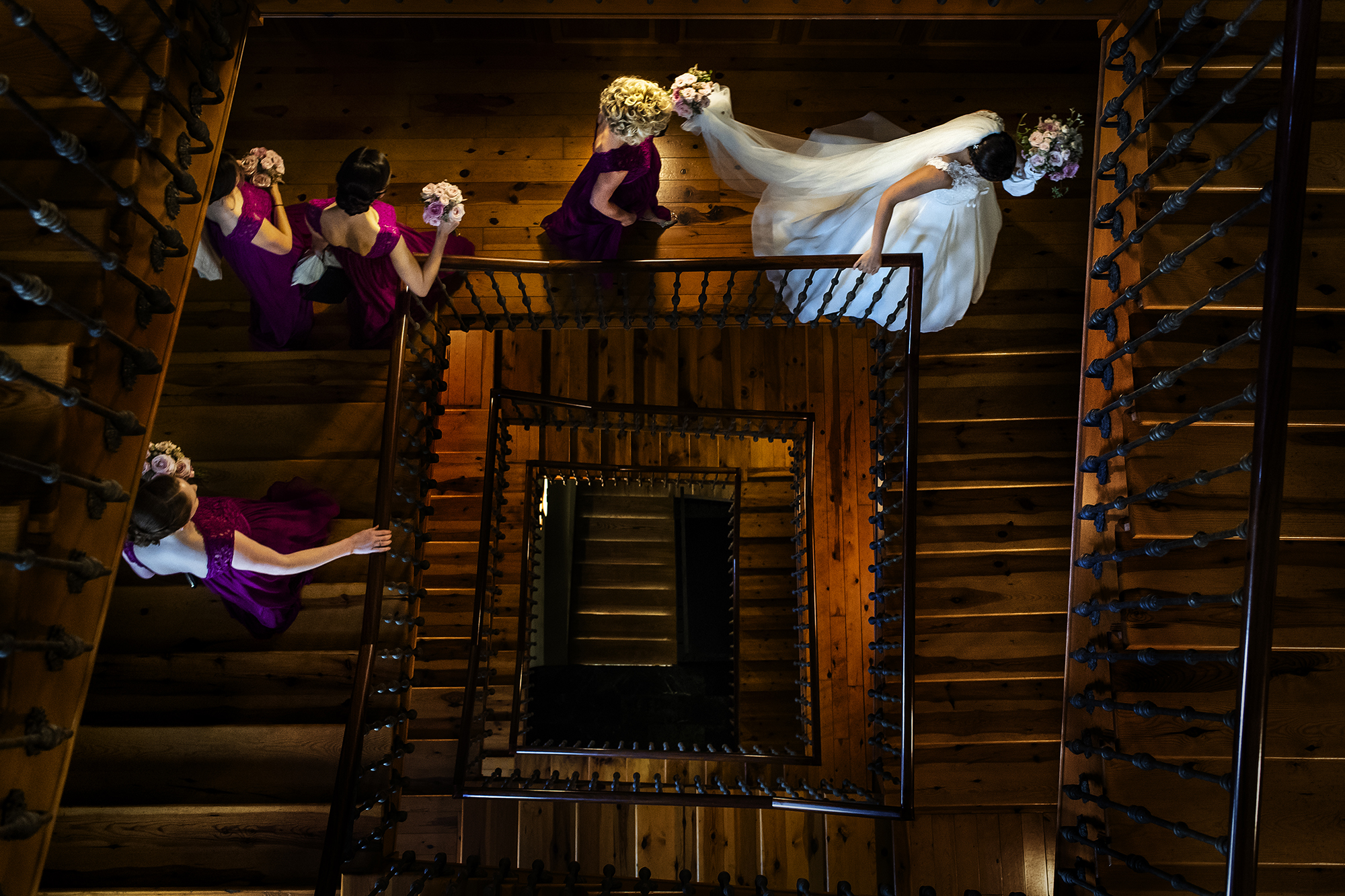 Bridal party descending spiral staircase - photo by Victor Lax