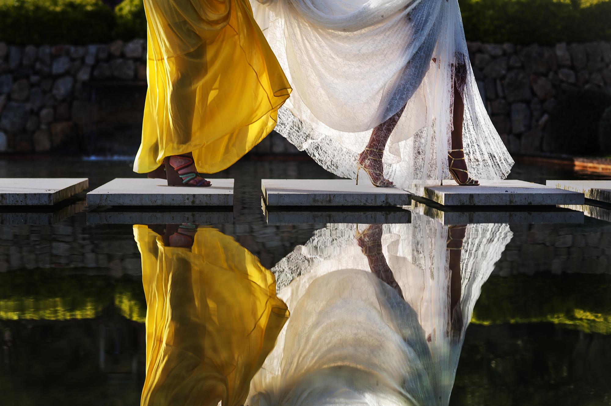 Bride and bridesmaid walking across water