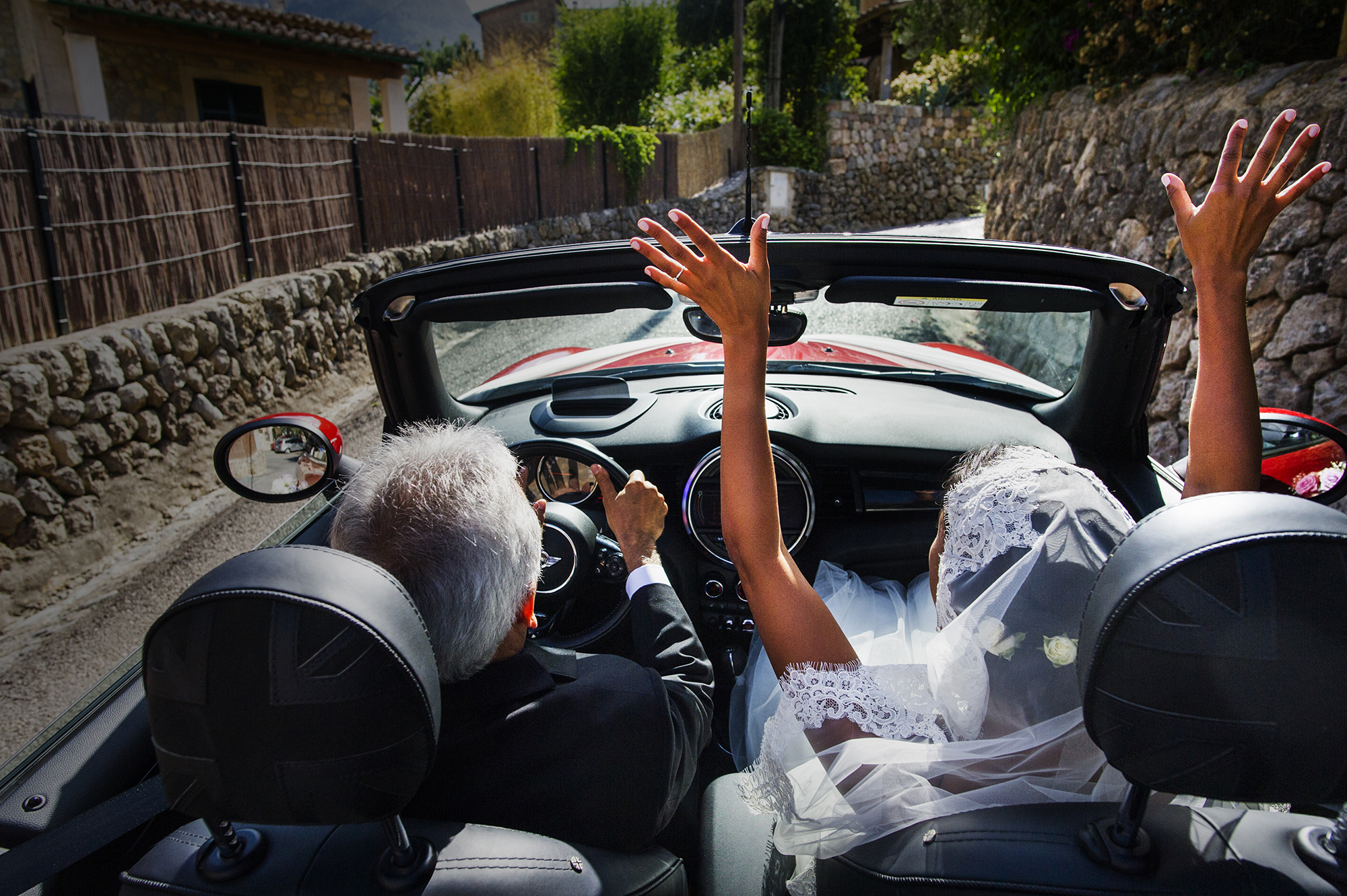 Bride and groom driving down English village lane - photo by Victor Lax