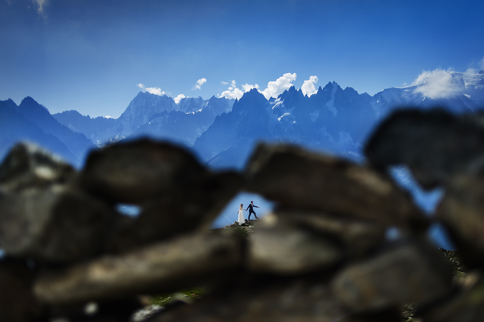Bride and groom framed in rocks with mountain backdrop - photo by Victor Lax