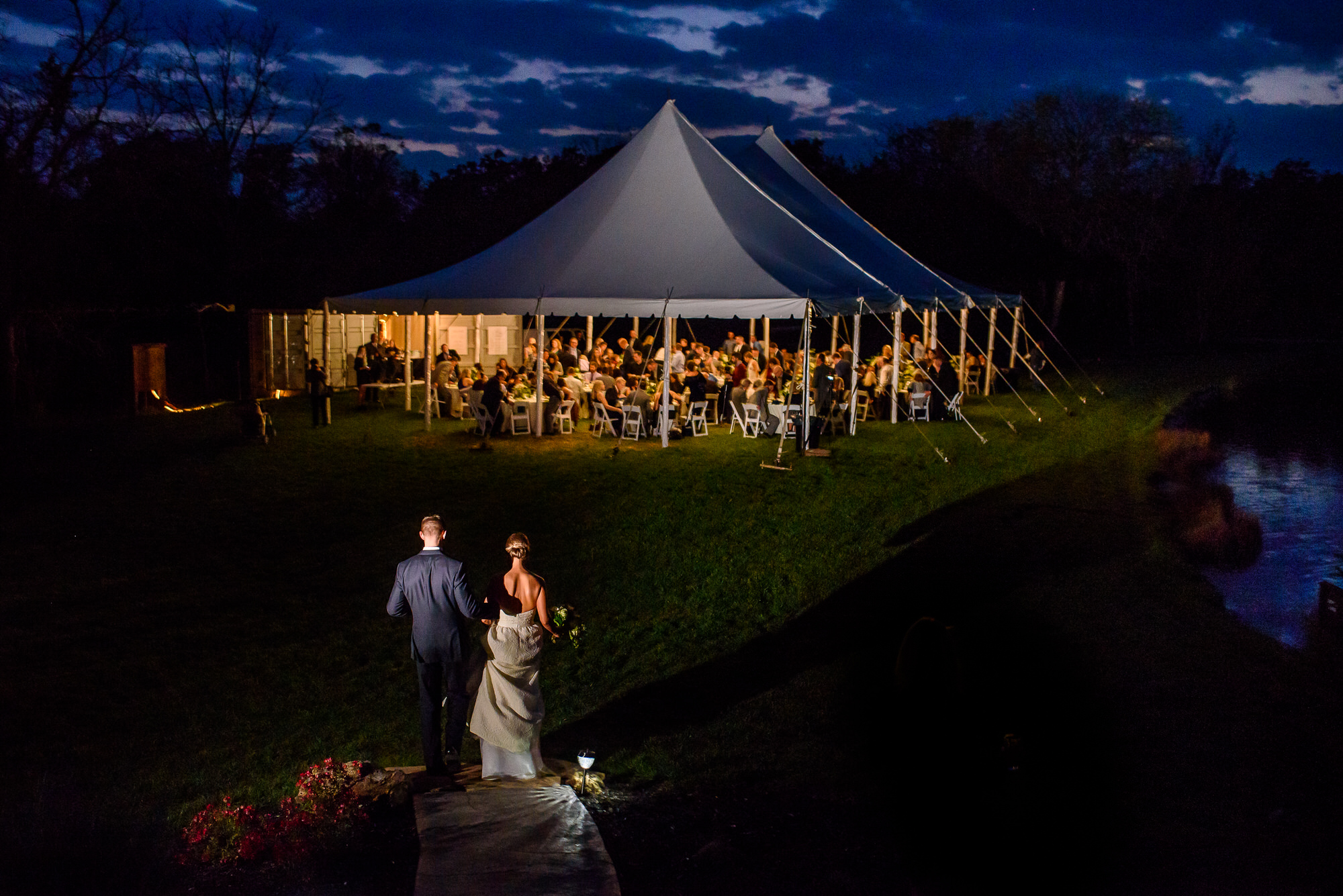 Bride and groom arrive at tented wedding reception - Photo by Tyler Wirken
