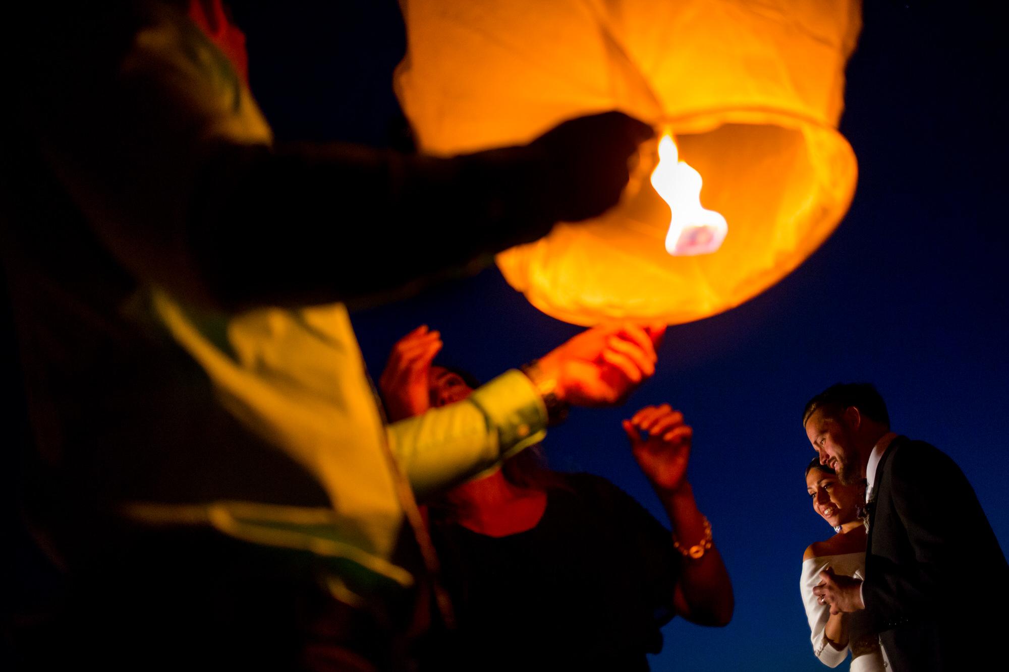 Couple lit by lantern - Photo by Tyler Wirken