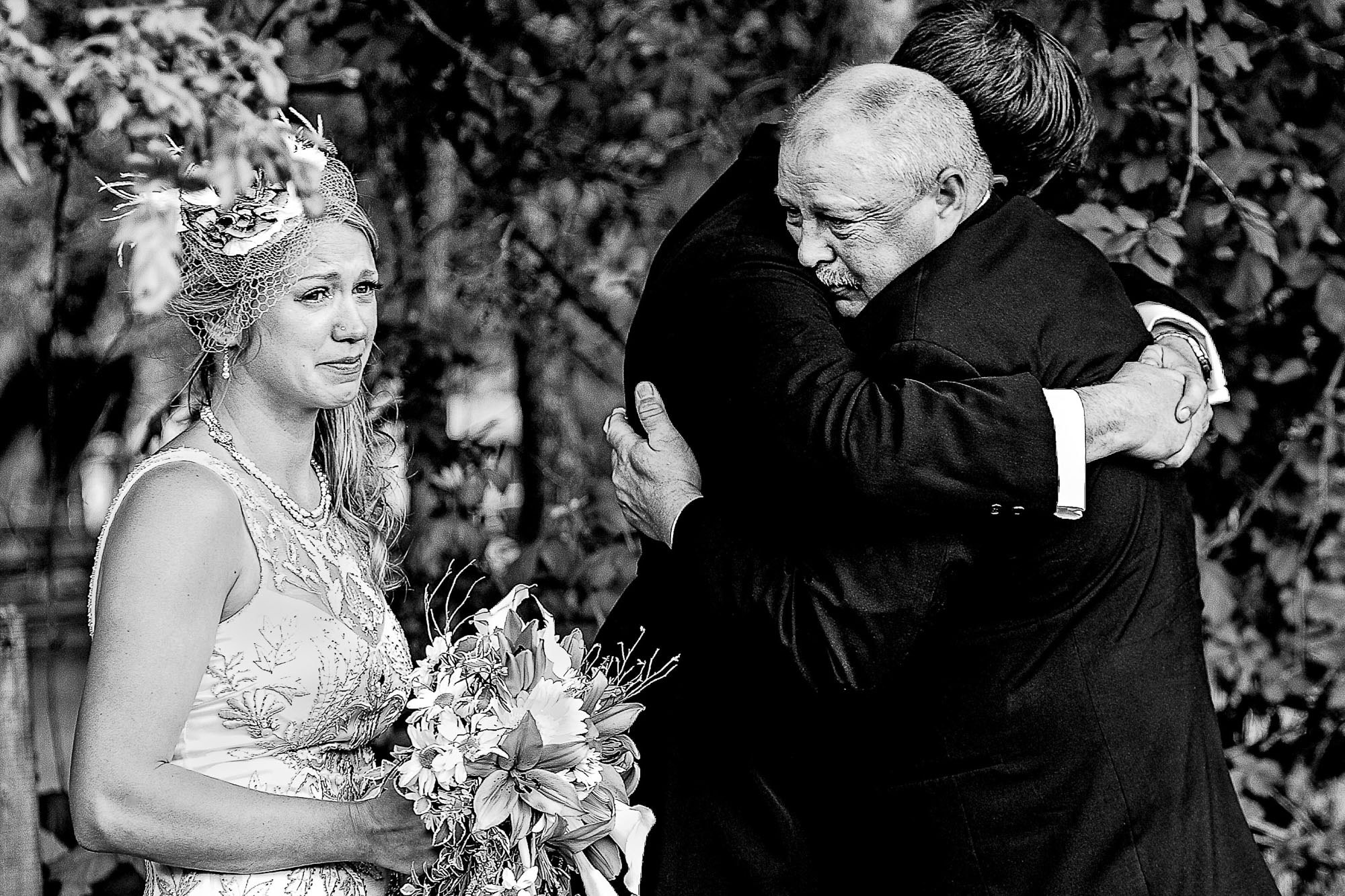 Bride cries while father hugs groom photo by JOS Studios : Jos and Tree Woodsmith