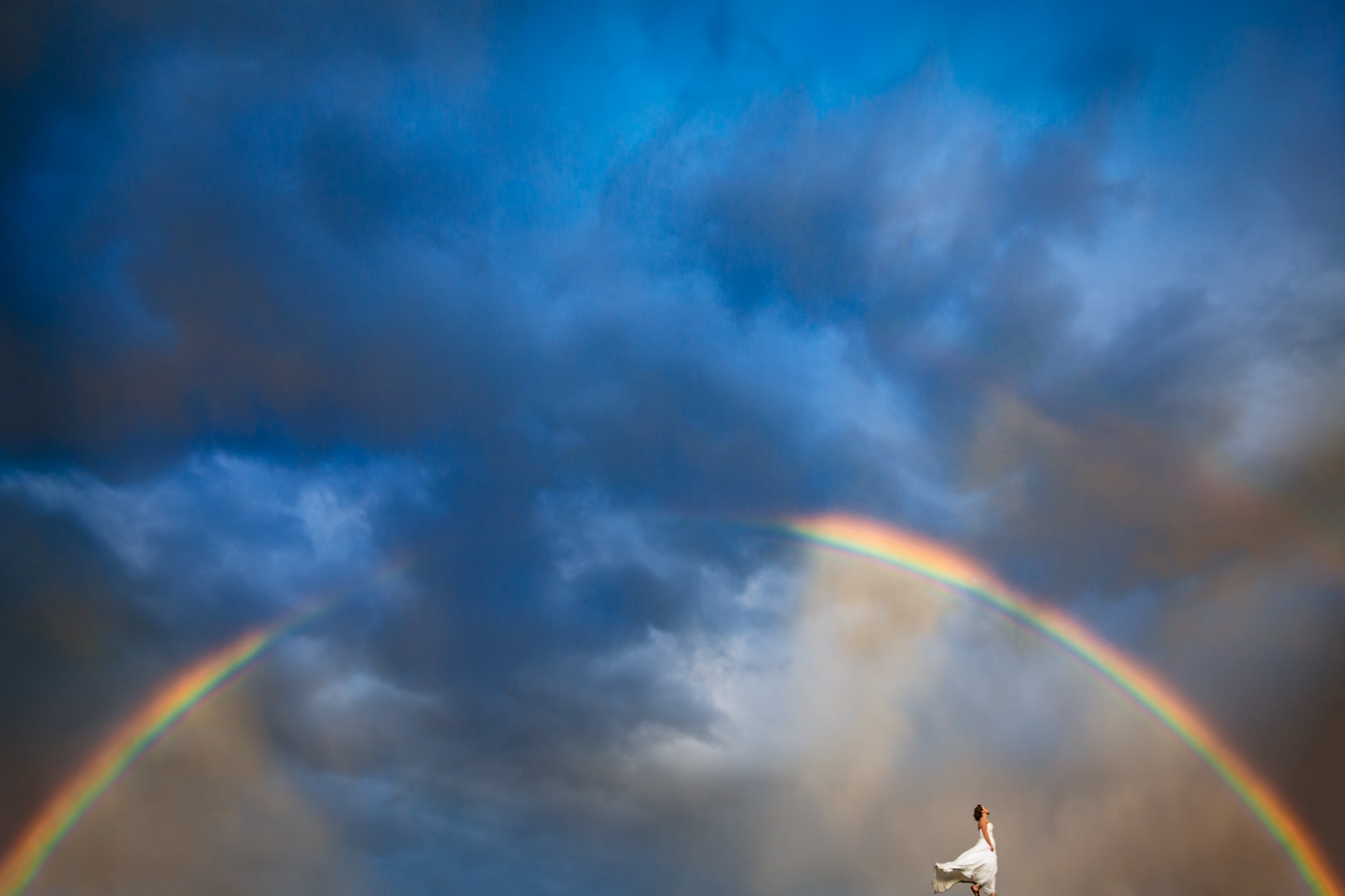Bride faces rainbow on windy hill - photo by Two Mann Studios