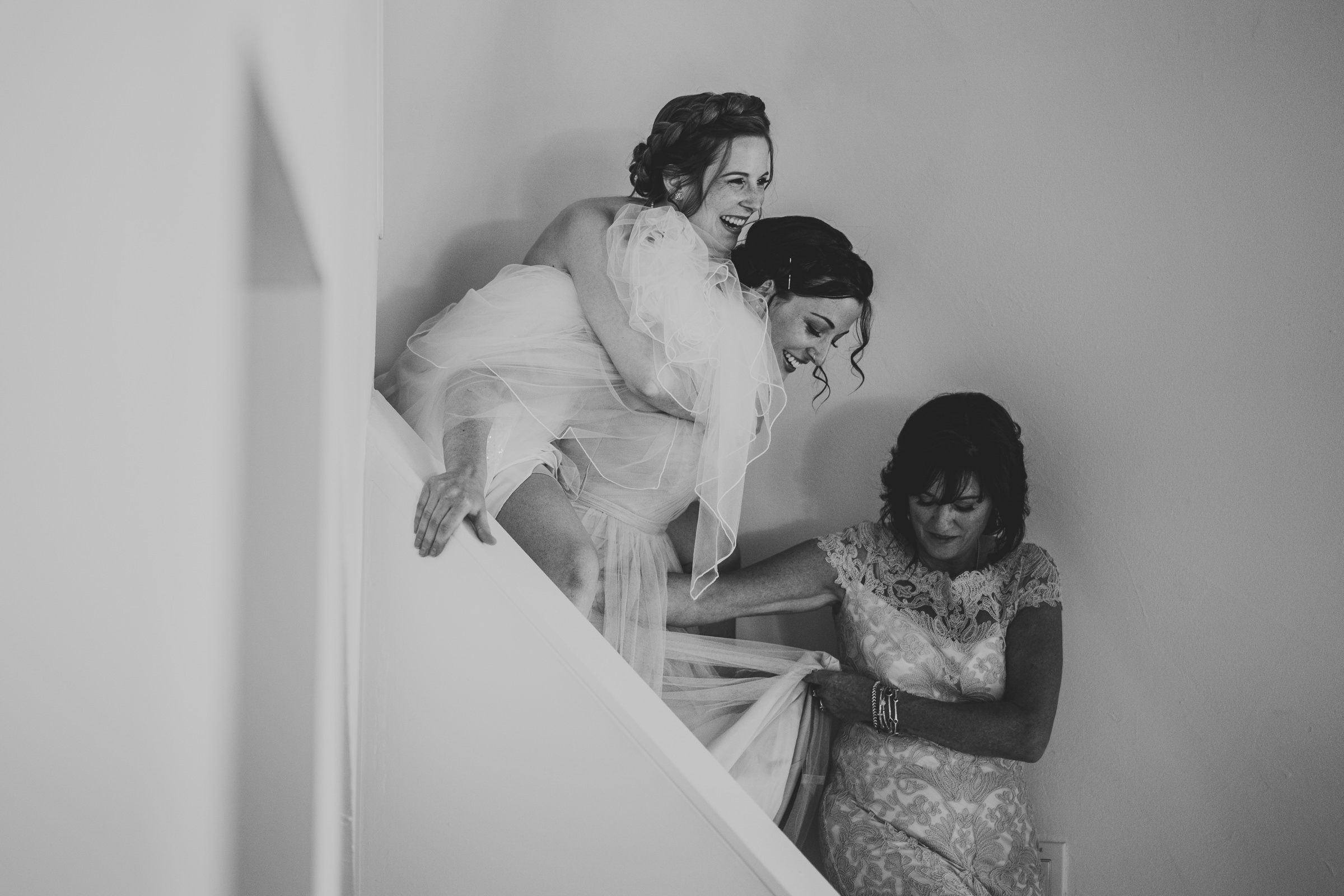 Bride getting piggy back down stairs - photo by Sam Hurd - DC