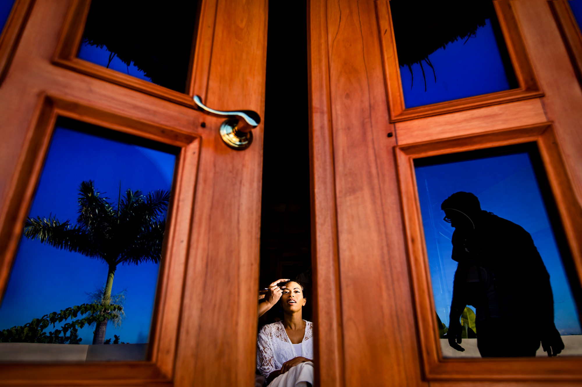 Bride gets ready seen through double doors - photo by Two Mann Studios