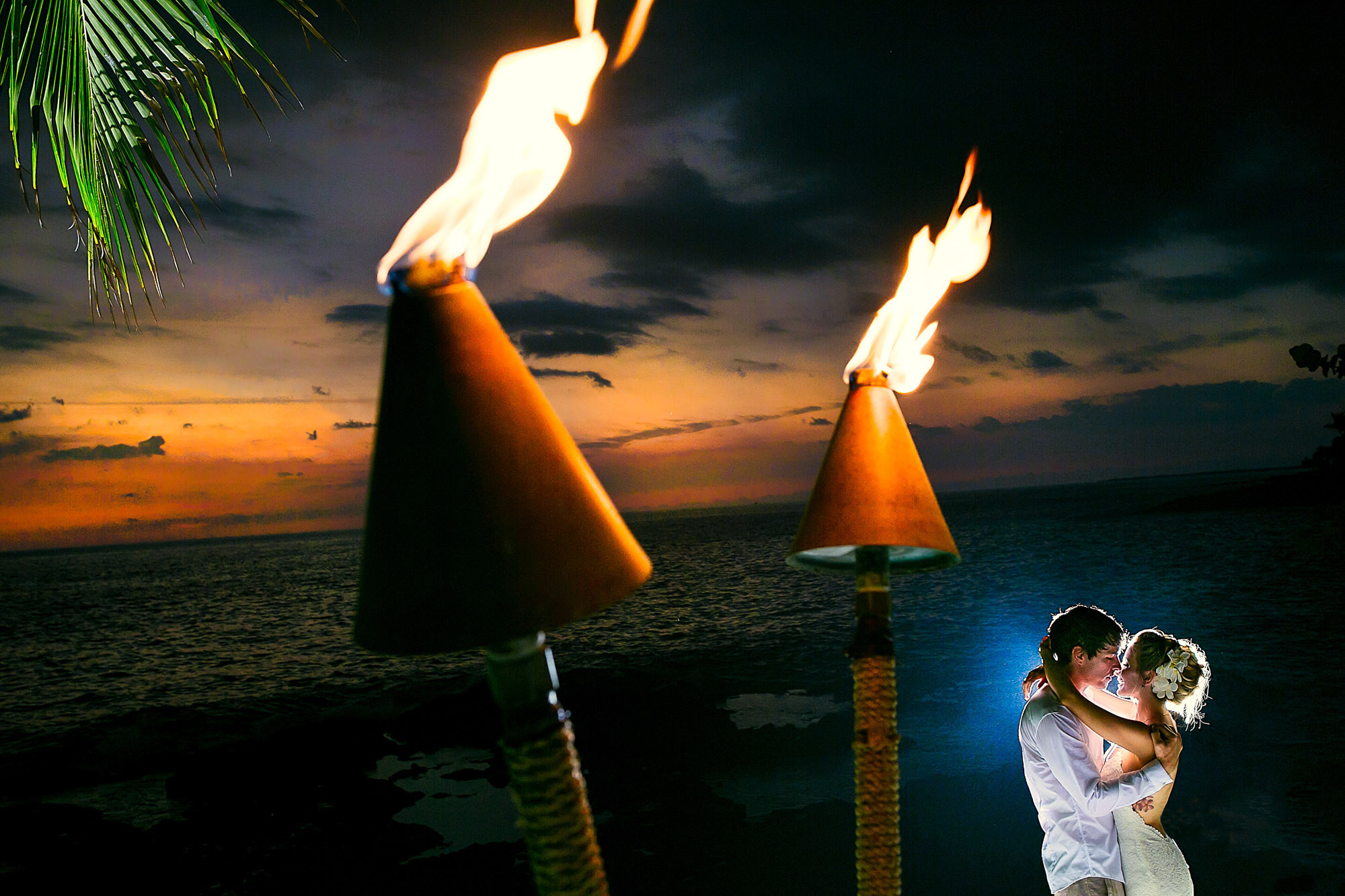 Bride and groom under tiki torch photo by JOS Studio: Jos and Tree
