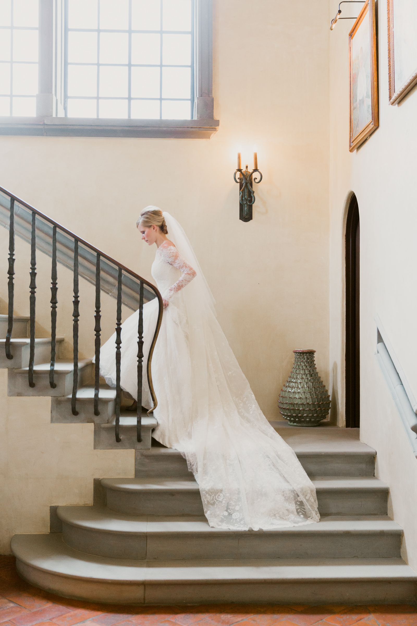 Bride in lace gown with long train ascends stairway - photo by Corbin Gurkin