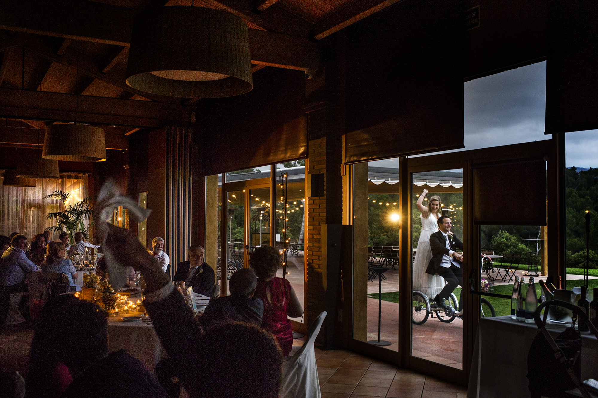 Bride riding on bike with groom entering reception - photo by Victor Lax