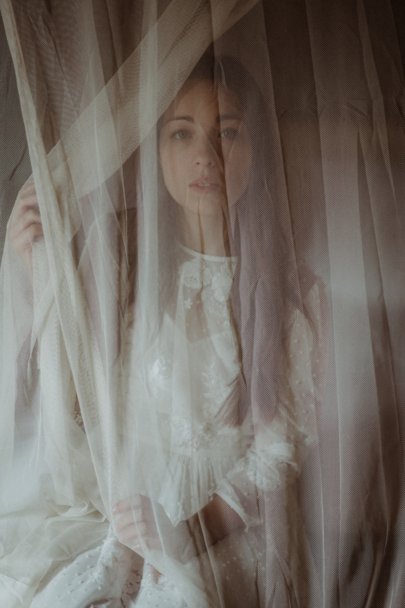 Portrait of bride looking through gauze drape - photo by the Kitcheners - Scotland