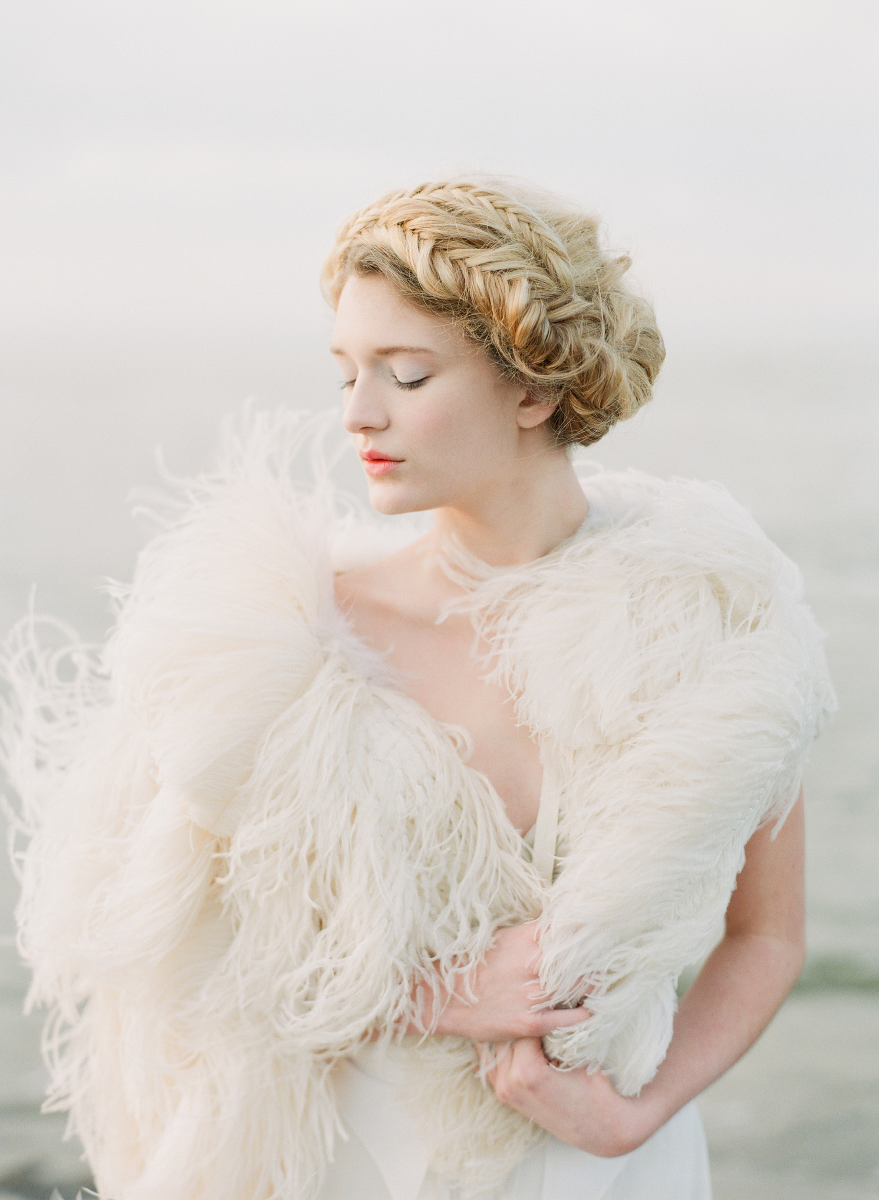 Bride with braided updo and feathered shawl - photo by Corbin Gurkin