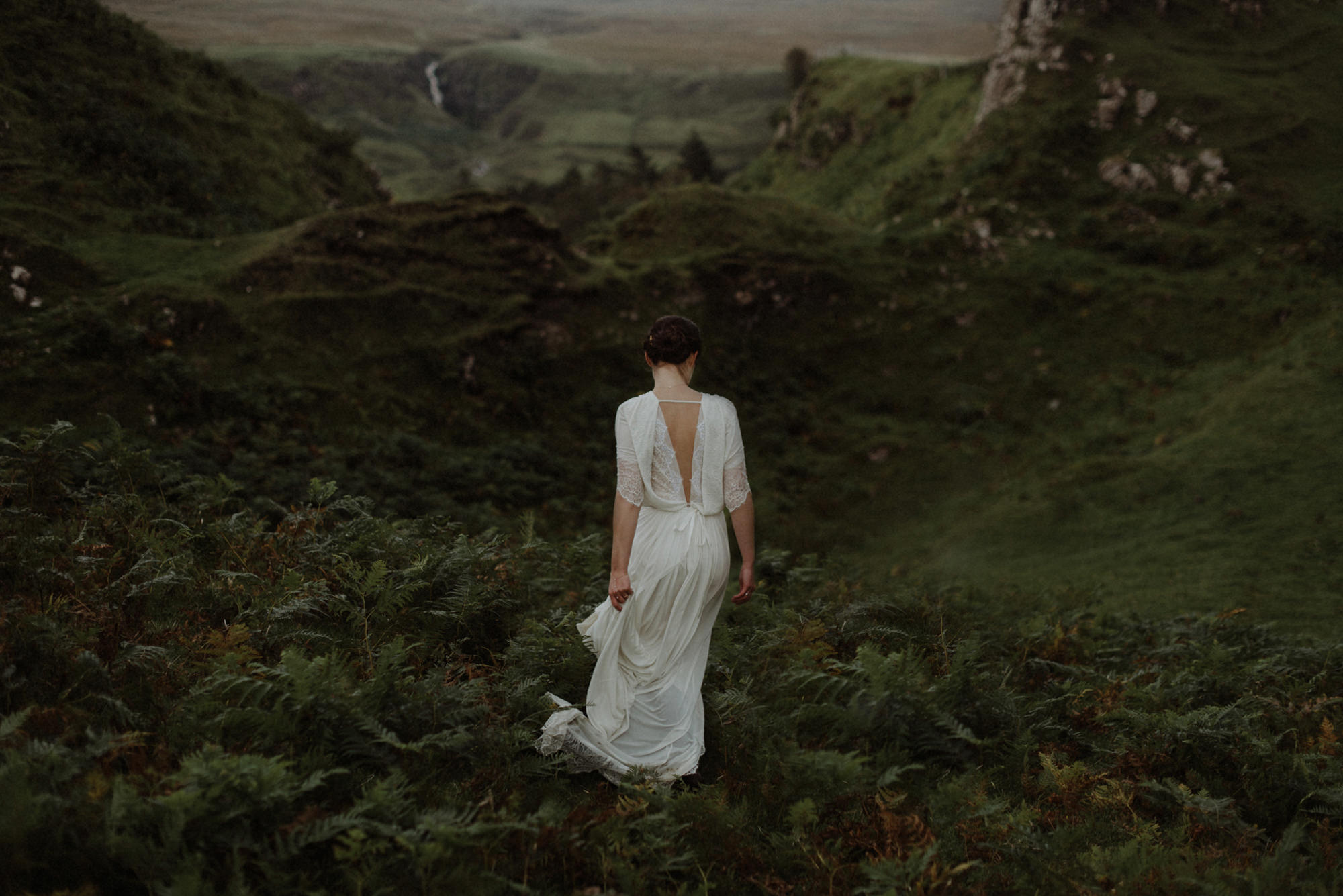 Bride in lace dress walking on green Glen - photo by the Kitcheners - Scotland