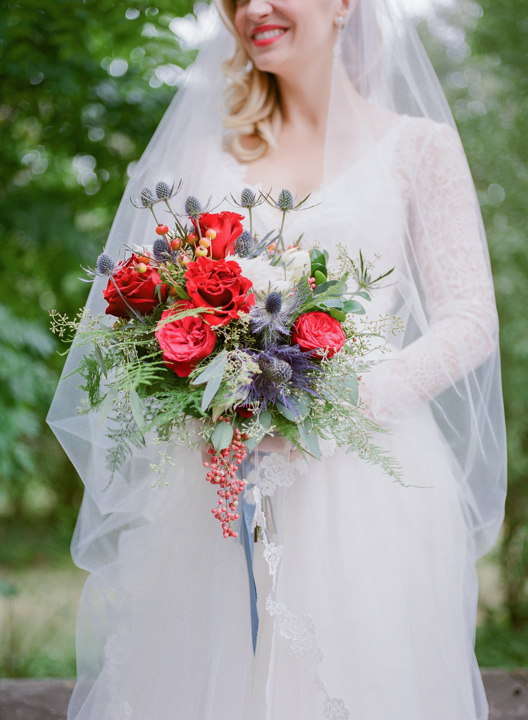 Bride with red rose and thistle cascading bouquet - photo by Corbin Gurkin