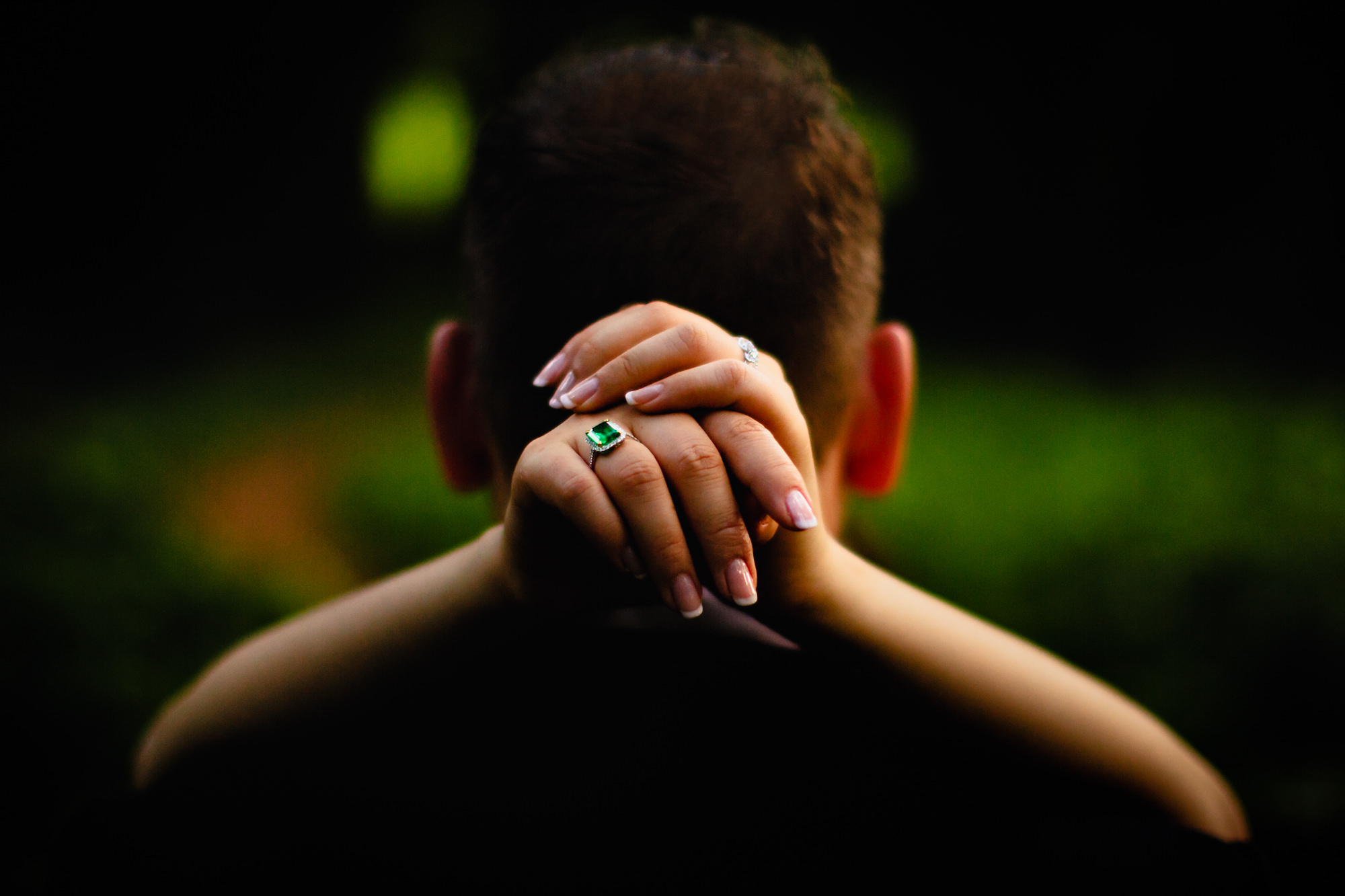 Bride with emerald ring  embracing groom's neck - photo by Two Mann Studios