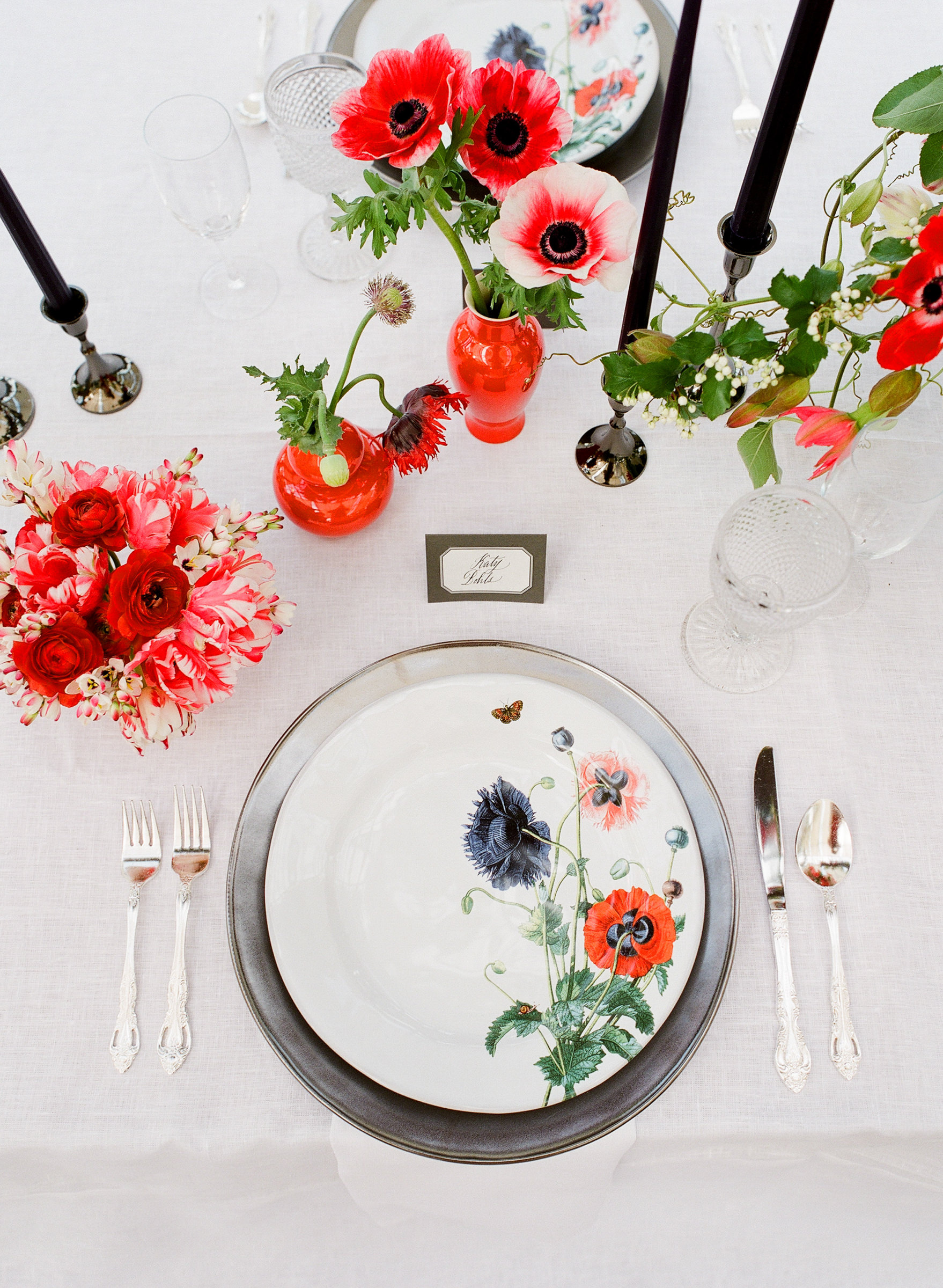 Brigh floral plates and red floral centerpieces - photo by Corbin Gurkin
