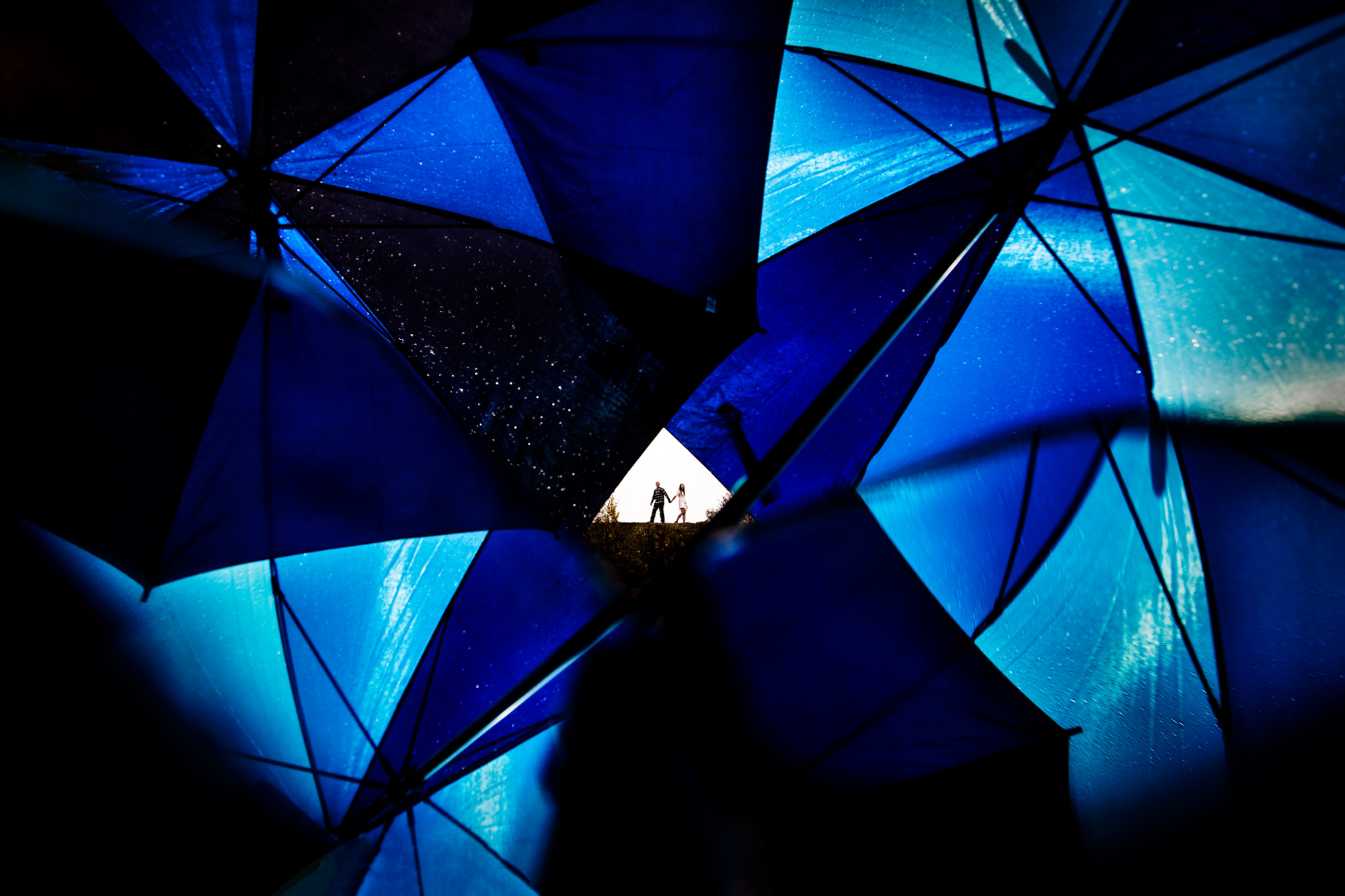 Couple behind geometric design of blue umbrellas - photo by Two Mann Studios
