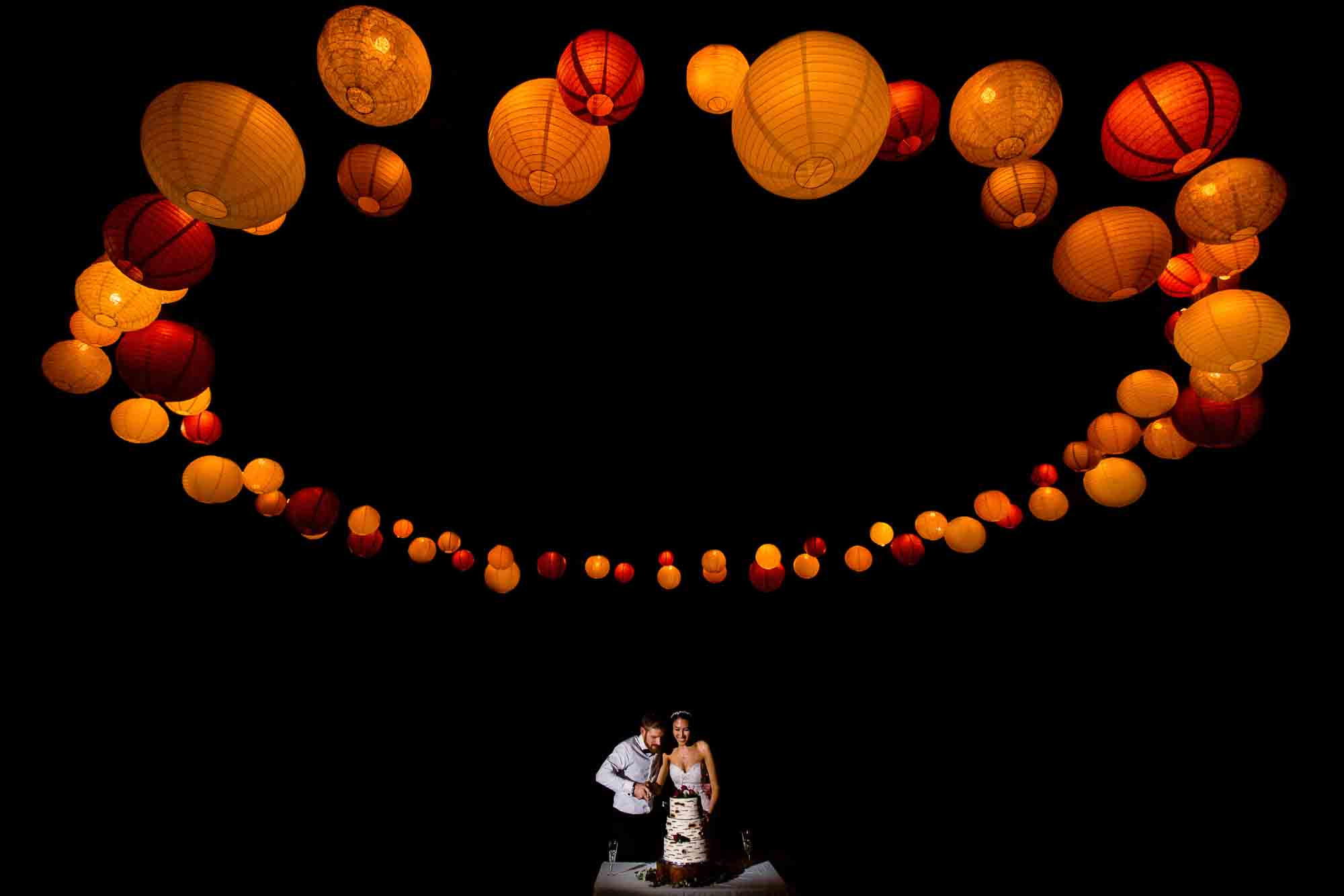 Couple cuts cake under golden lantern photo by JOS Studios : Jos and Tree Woodsmith