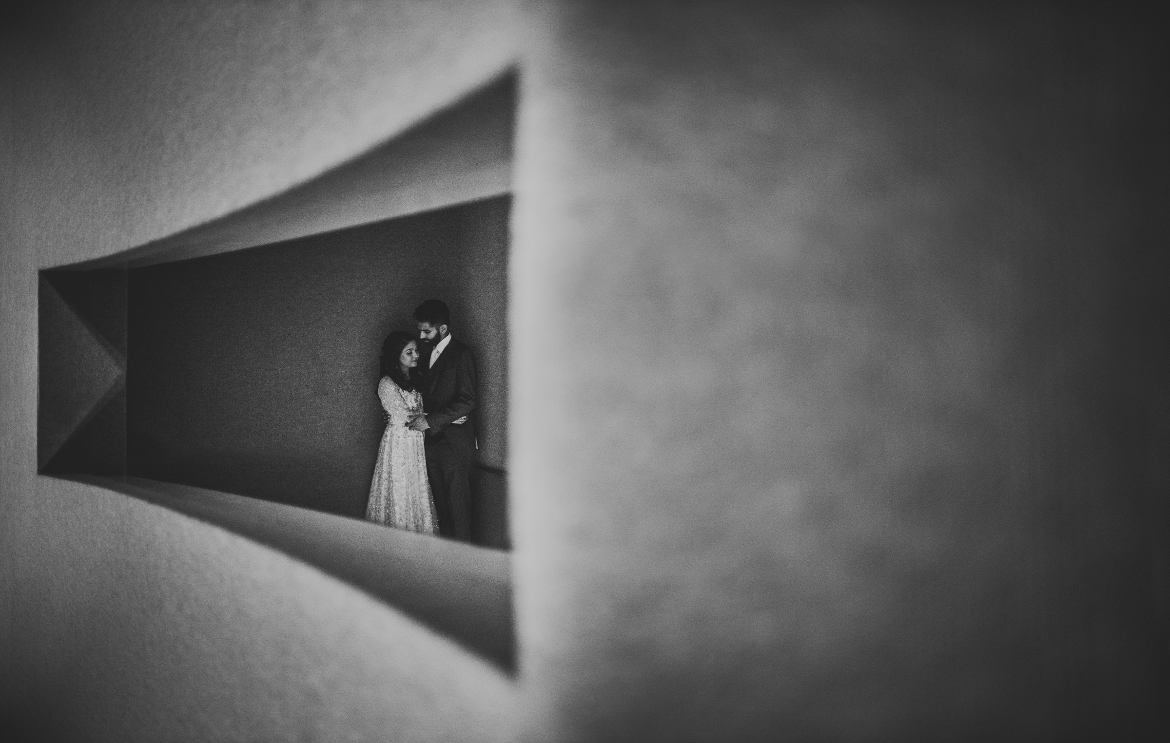 Couple embraces in curved stone window - photo by Sam Hurd - DC