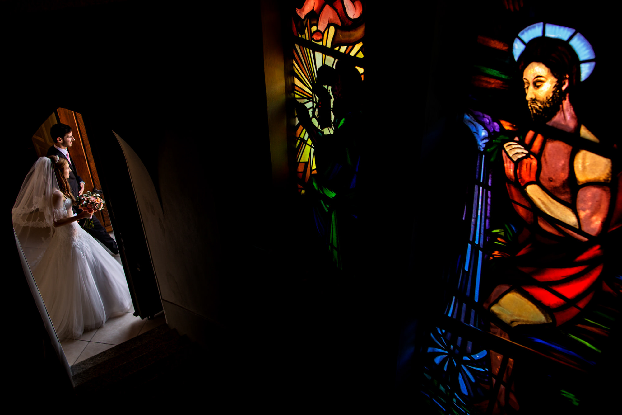 Couple exits church with stained glass window - photo by Two Mann Studios