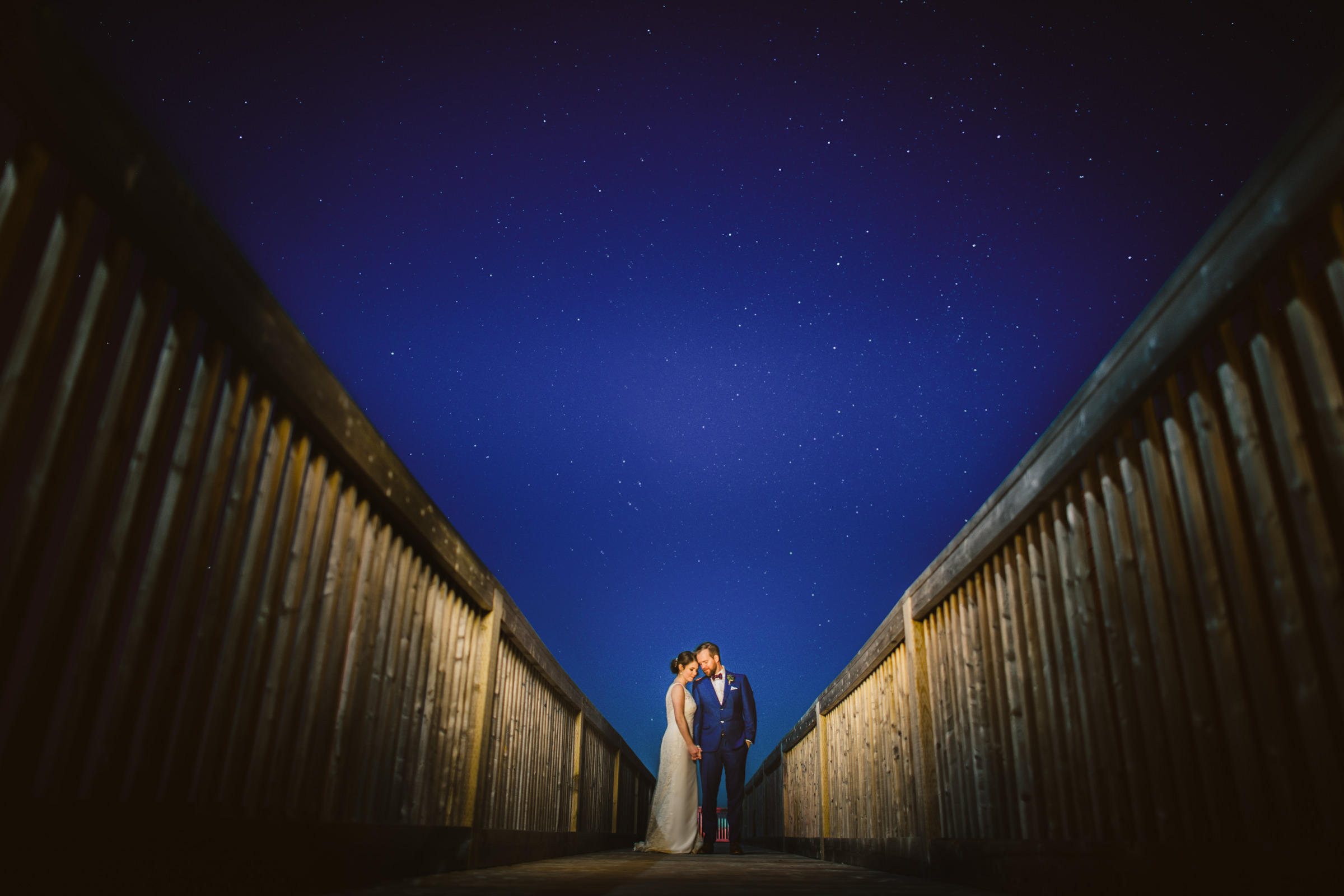 Couple under stars on wooden bridge - photo by Sam Hurd - DC