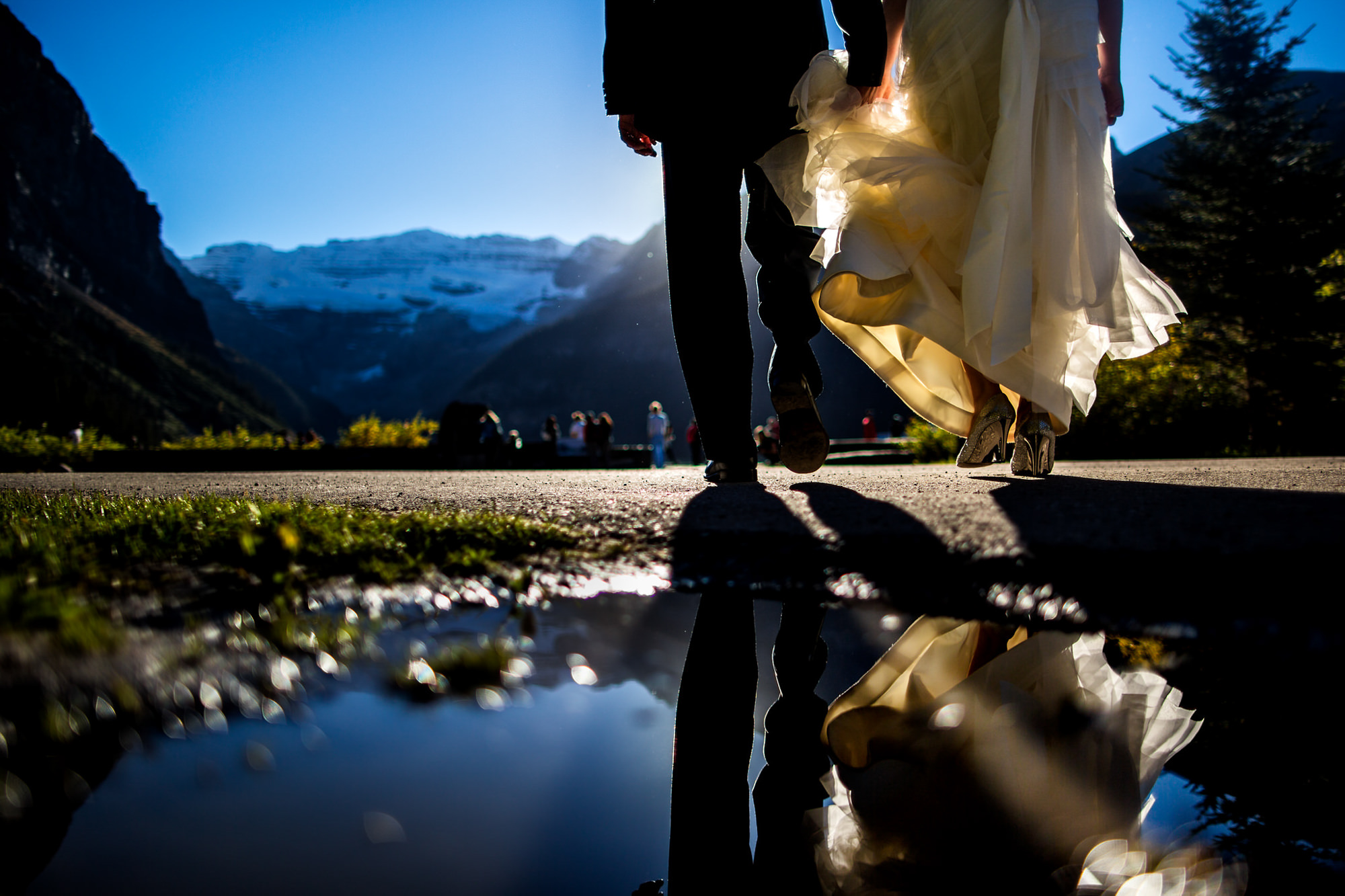 Couple reflected in puddle walking toward guests - photo by Two Mann Studios