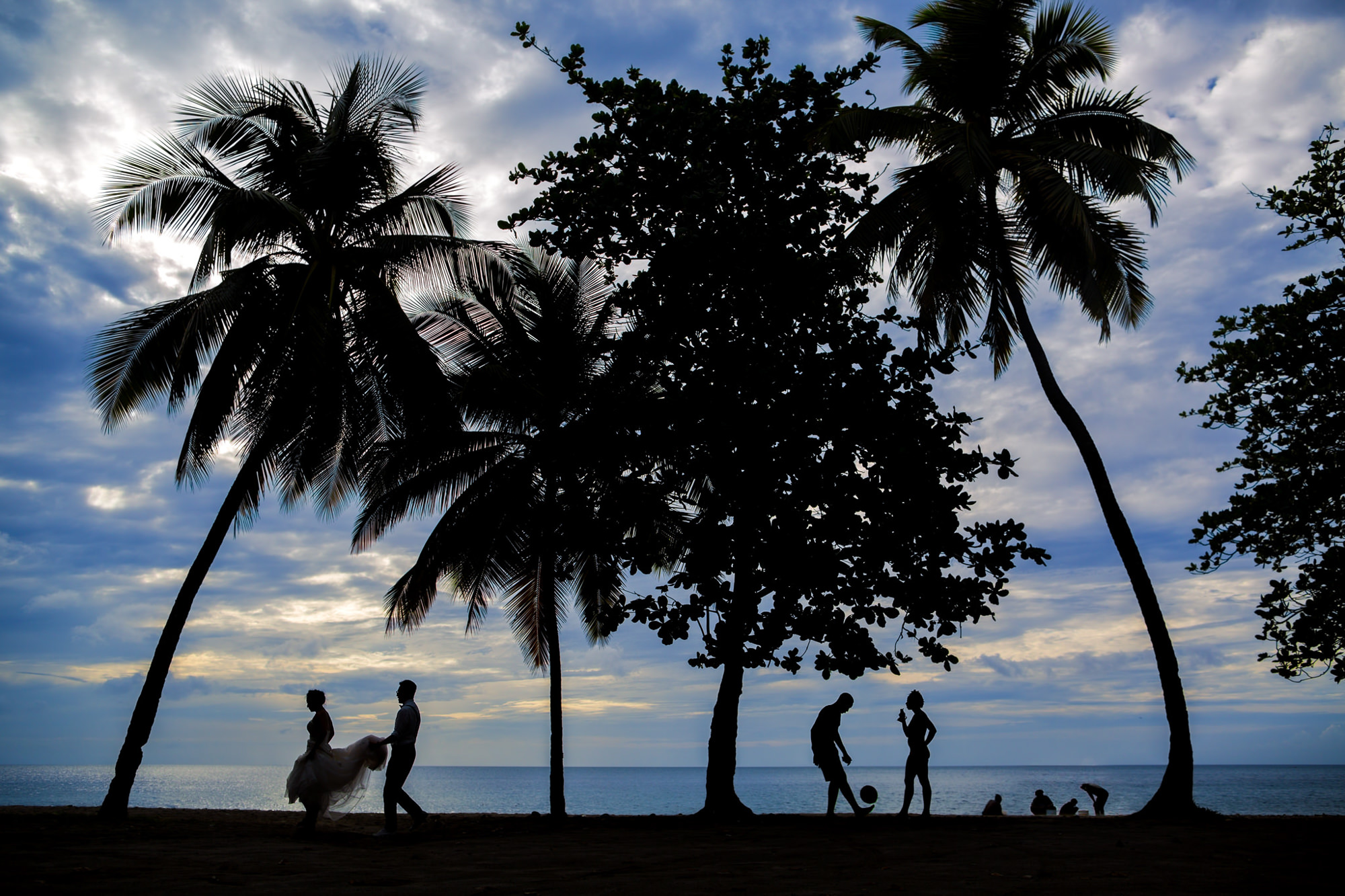 Couple walks along beach with bystanders playing - photo by Two Mann Studios