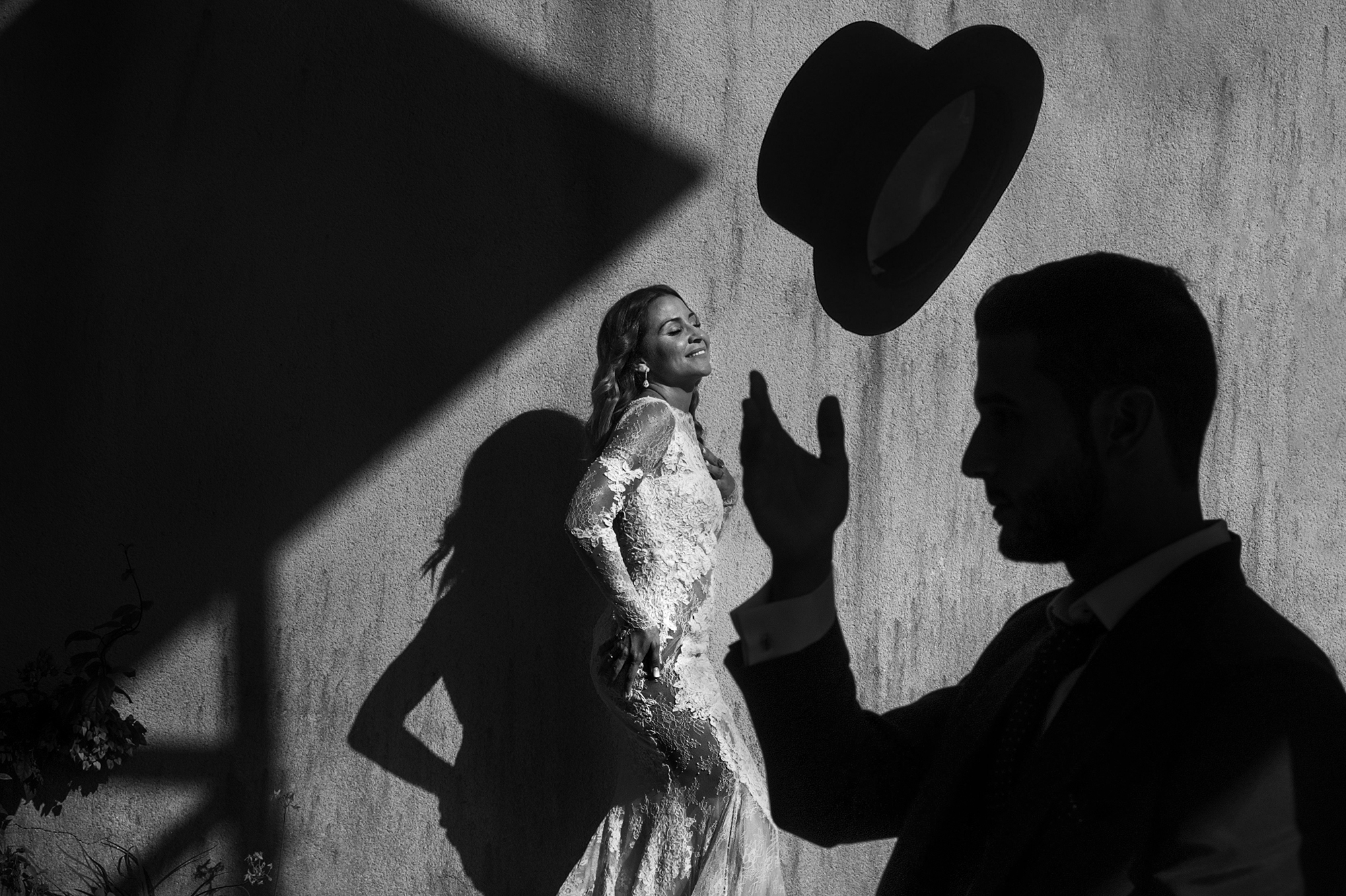 Bride with silhouetted groom and hat - photo by Victor Lax