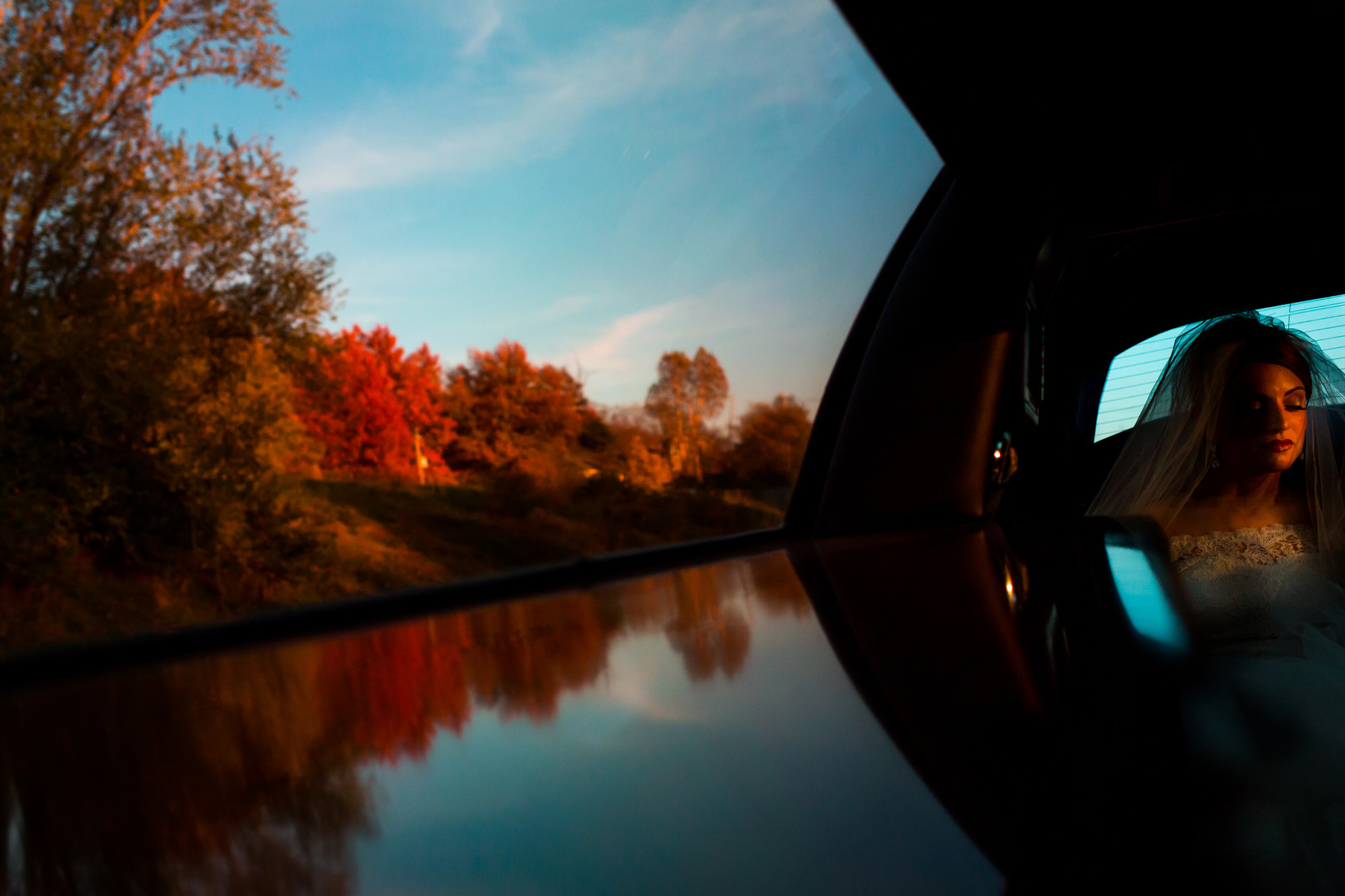 Bride in back seat of car driving along tree lined river - Photo by Tyler Wirken