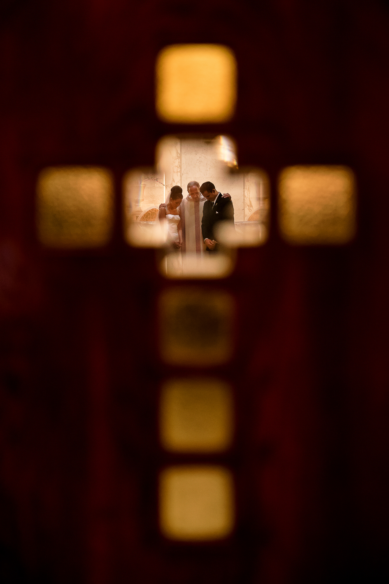 Ceremony blessing through cross window - photo by Tyler Wirken  - Kansas City