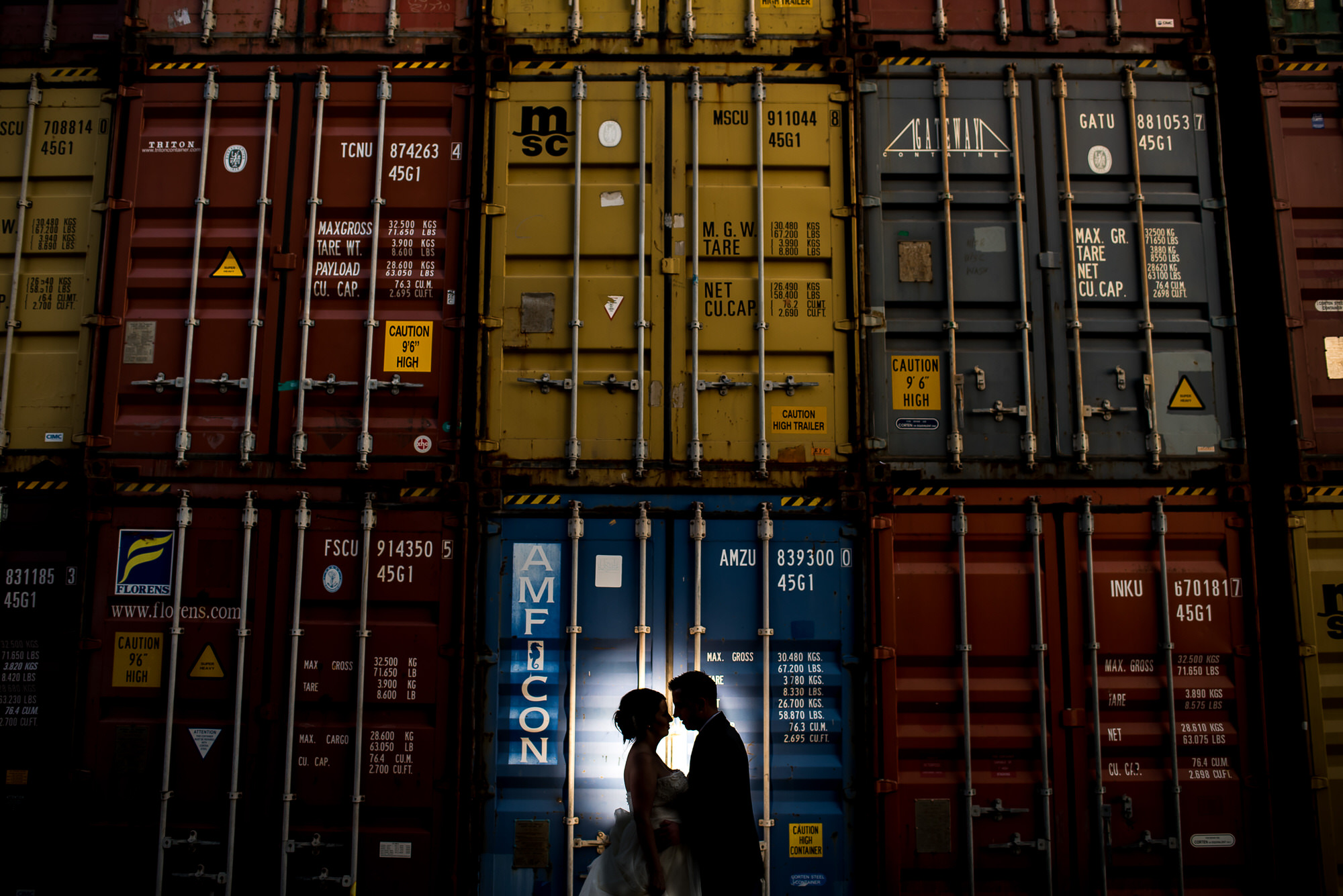 Silhouette of couple in front of stacked freight bins - photo by Tyler Wirken