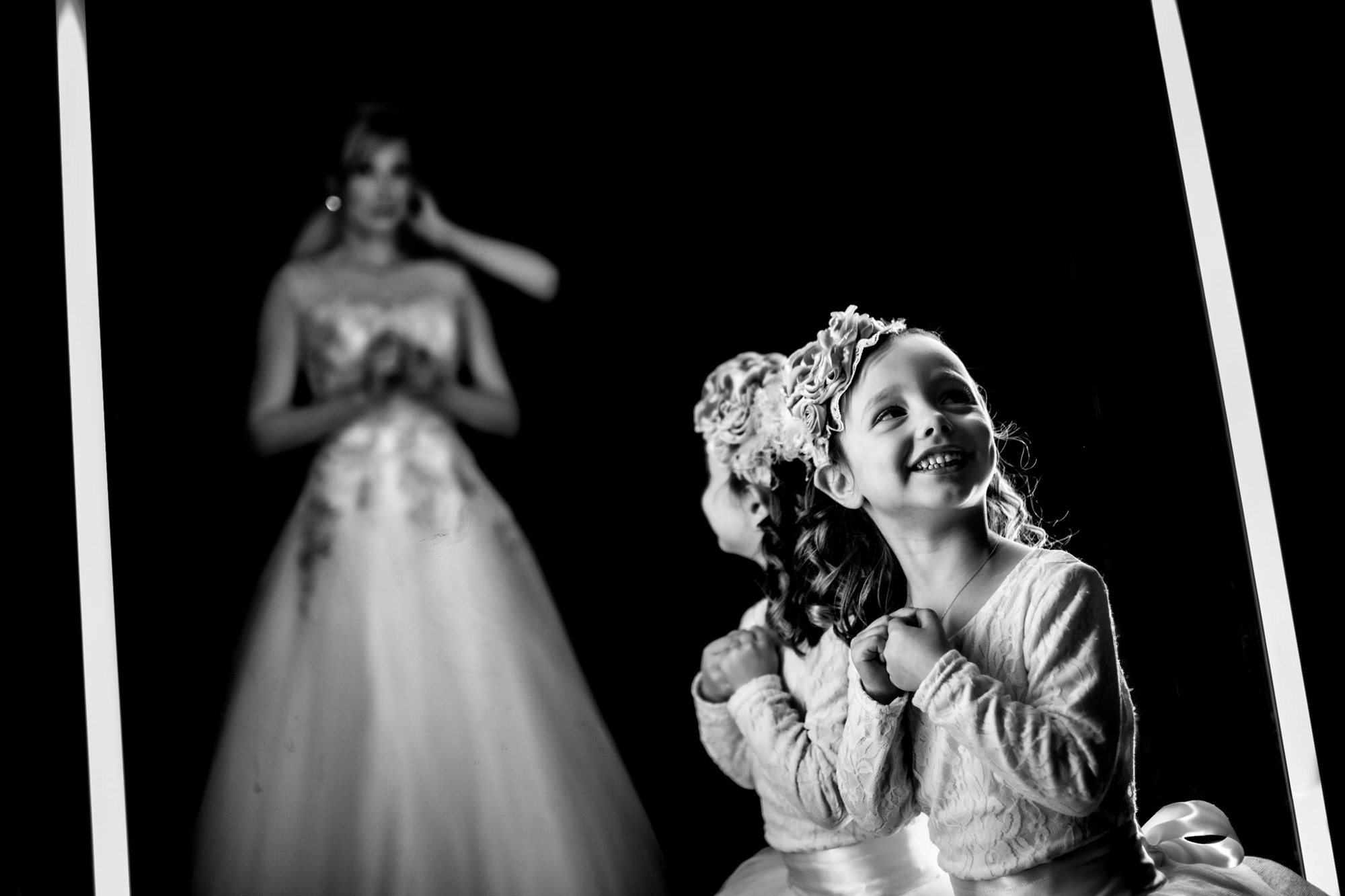 Delighted little girl in ornate hat looks lovingly at bride getting ready - photo by Two Mann Studios