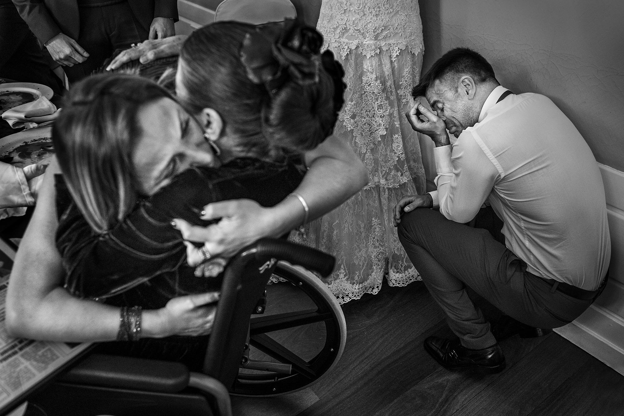 Emotional portrait of woman hugging woman in wheelchair - photo by Victor Lax