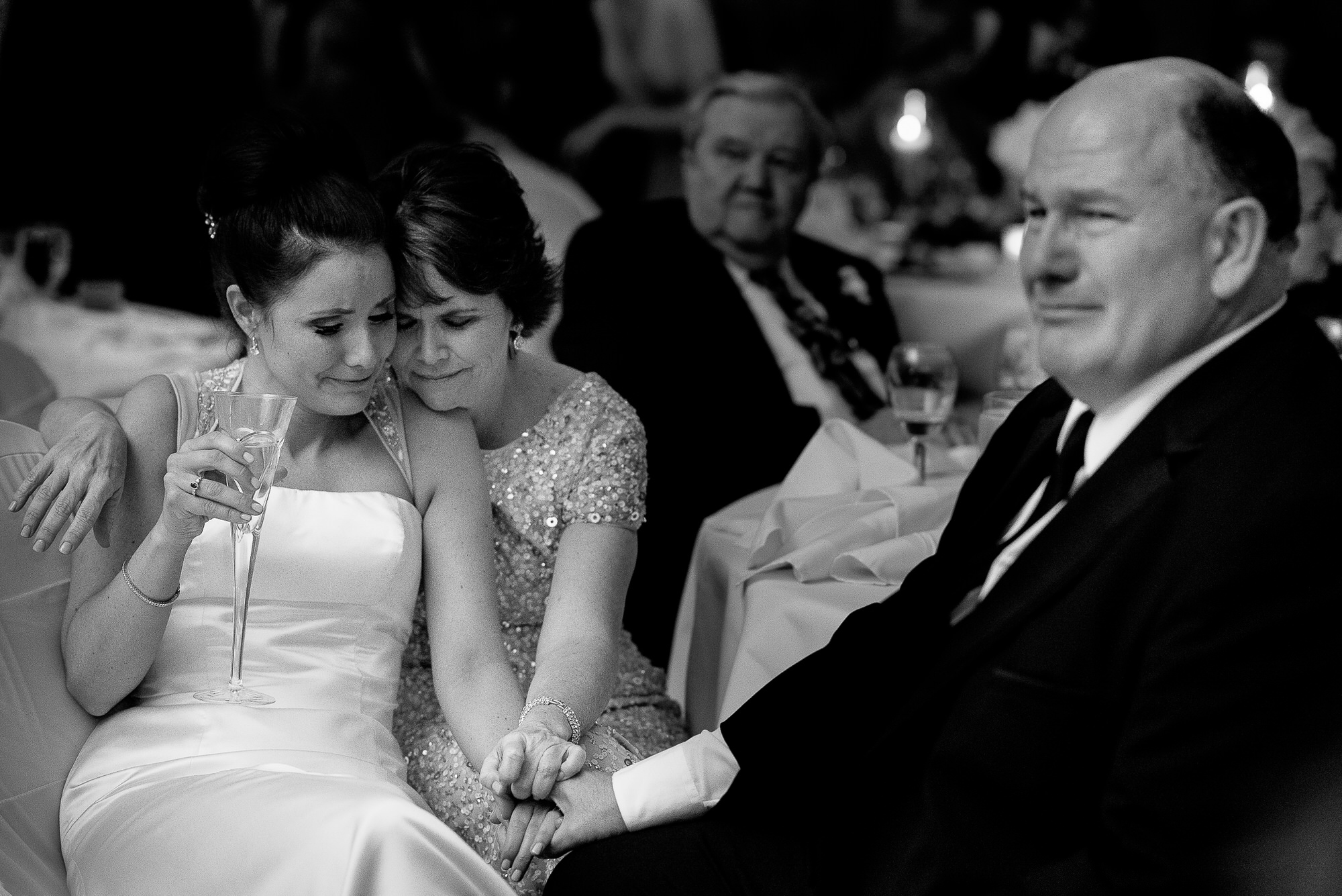Bride and her parents holding hands and crying - photo by Tyler Wirken