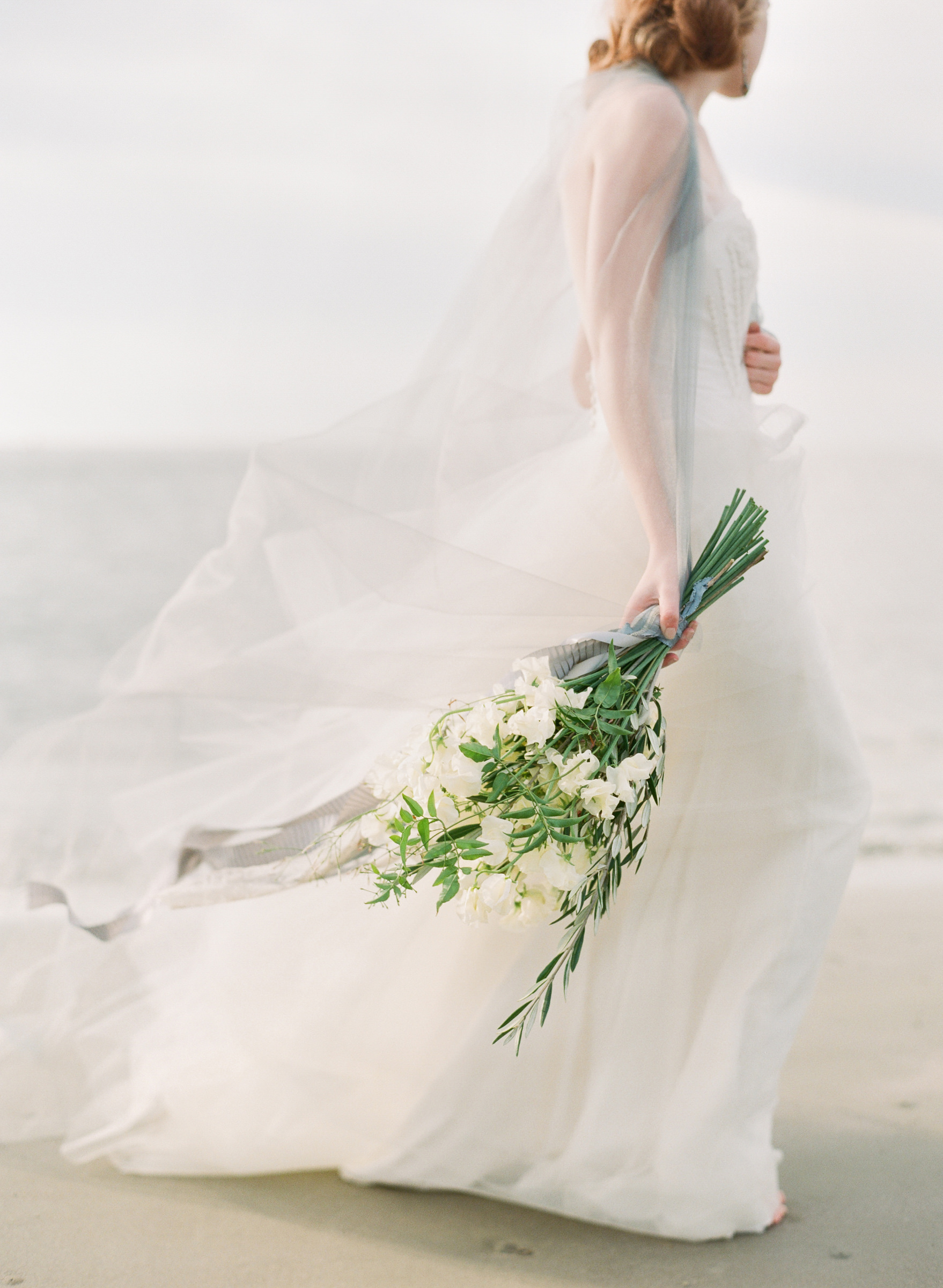 Ethereal photo of bride on beach with white lilly bouquet - photo by Corbin Gurkin